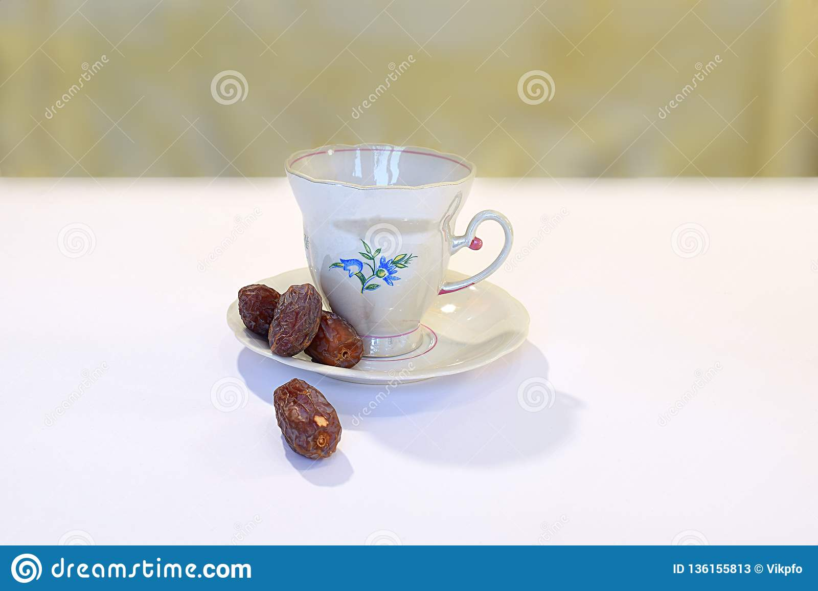 Dates and saucer with a cup on a white table