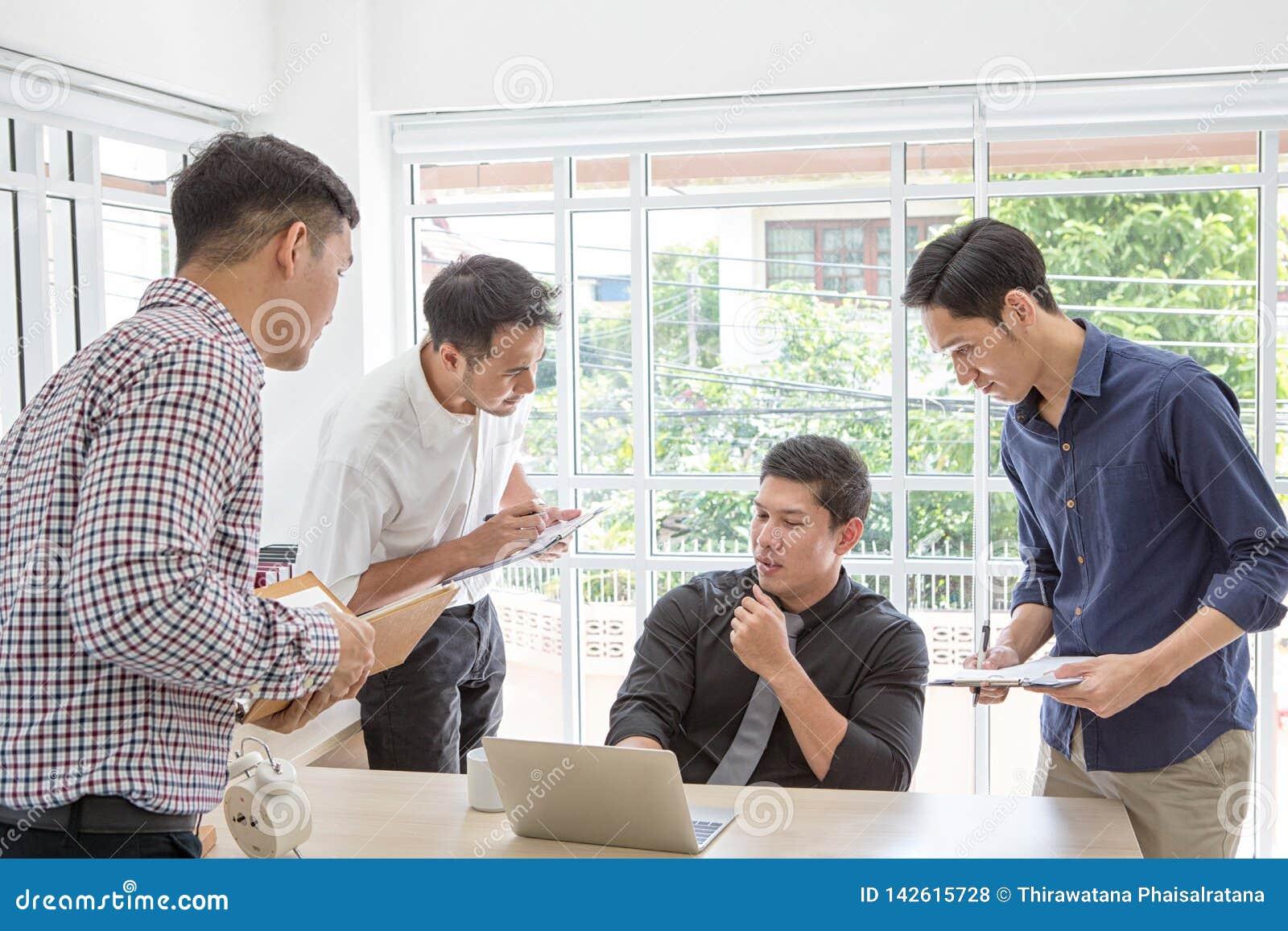 Dati plaining dell uomo d affari alla riunione Gente di affari che si incontra intorno allo scrittorio Gente asiatica Giovane uom