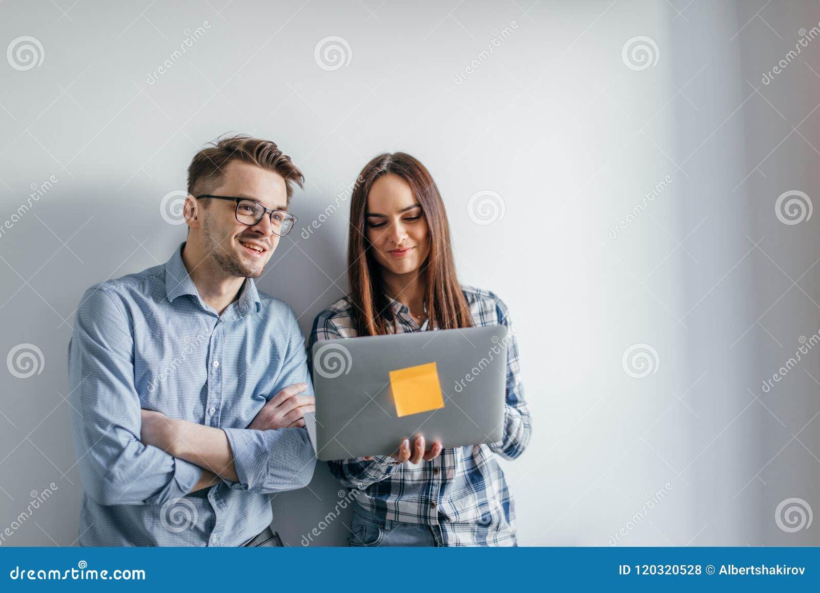 Dator för bärbar dator för lyckliga blandning-lopp par hållande, medan stå och fira som isoleras över grå väggbakgrund