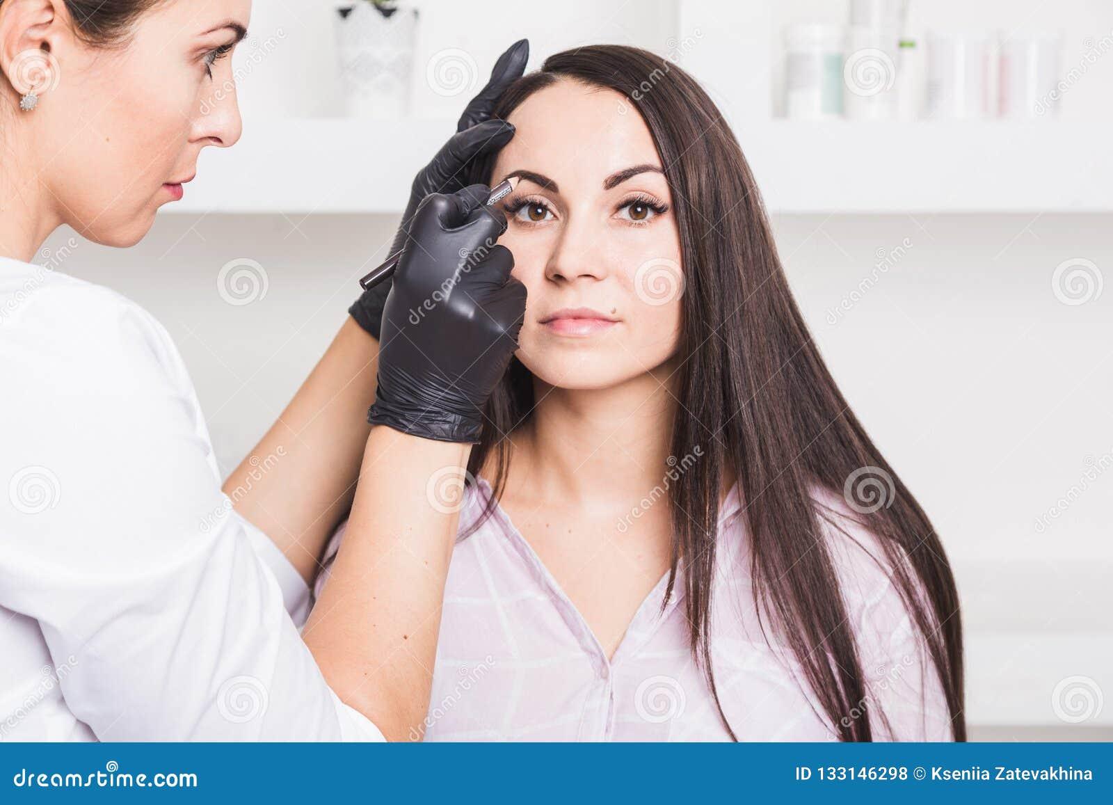 Dauerhaftes Make-up für Augenbrauen der schönen jungen Frau im Schönheitssalon