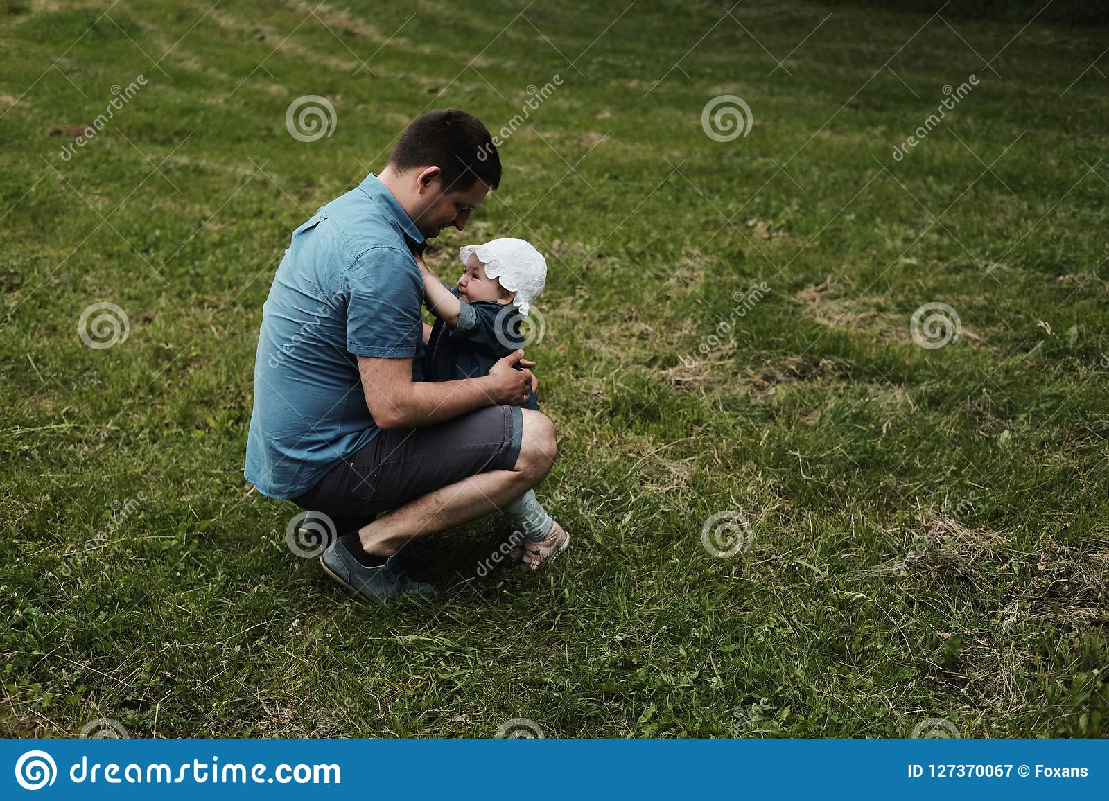 A daughter and a father huging in a park