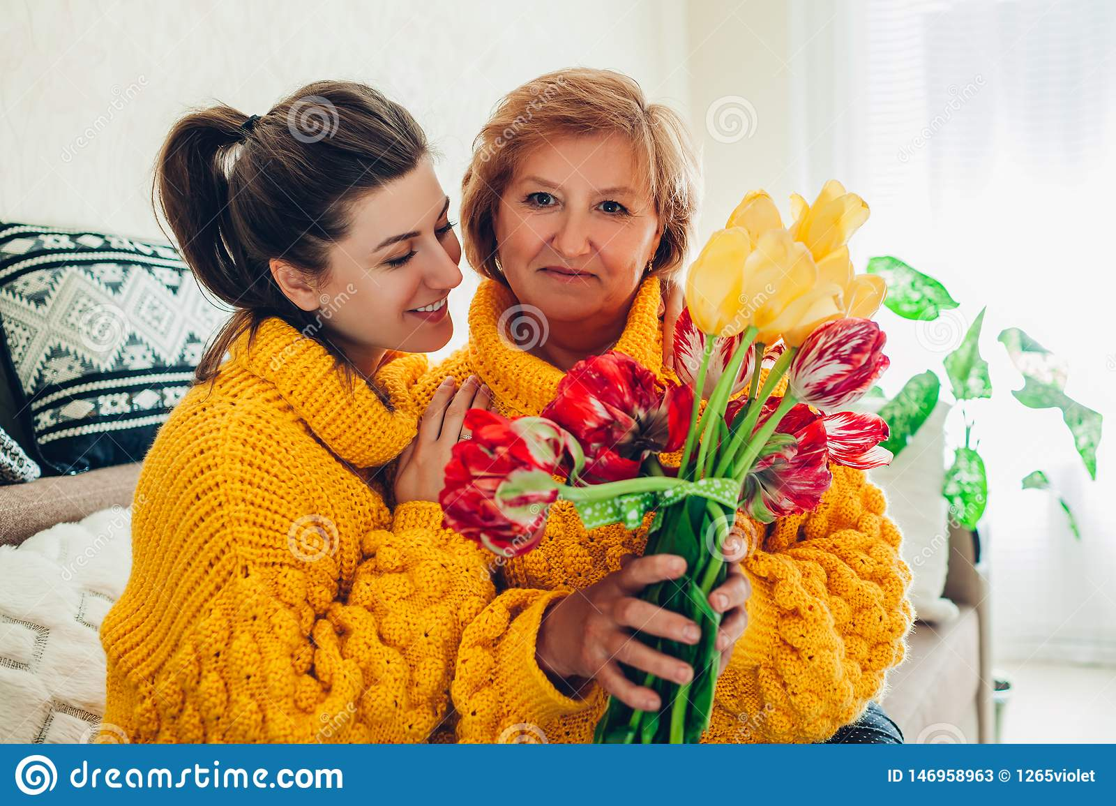 Daughter giving her mother bouquet of flowers at home as Mother`s day present wearing similar sweaters