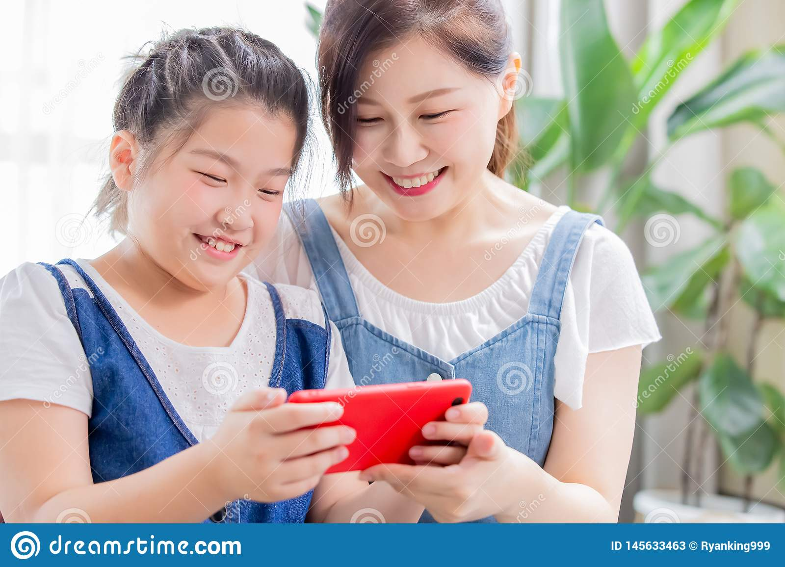 Daughter and mom play mobile game