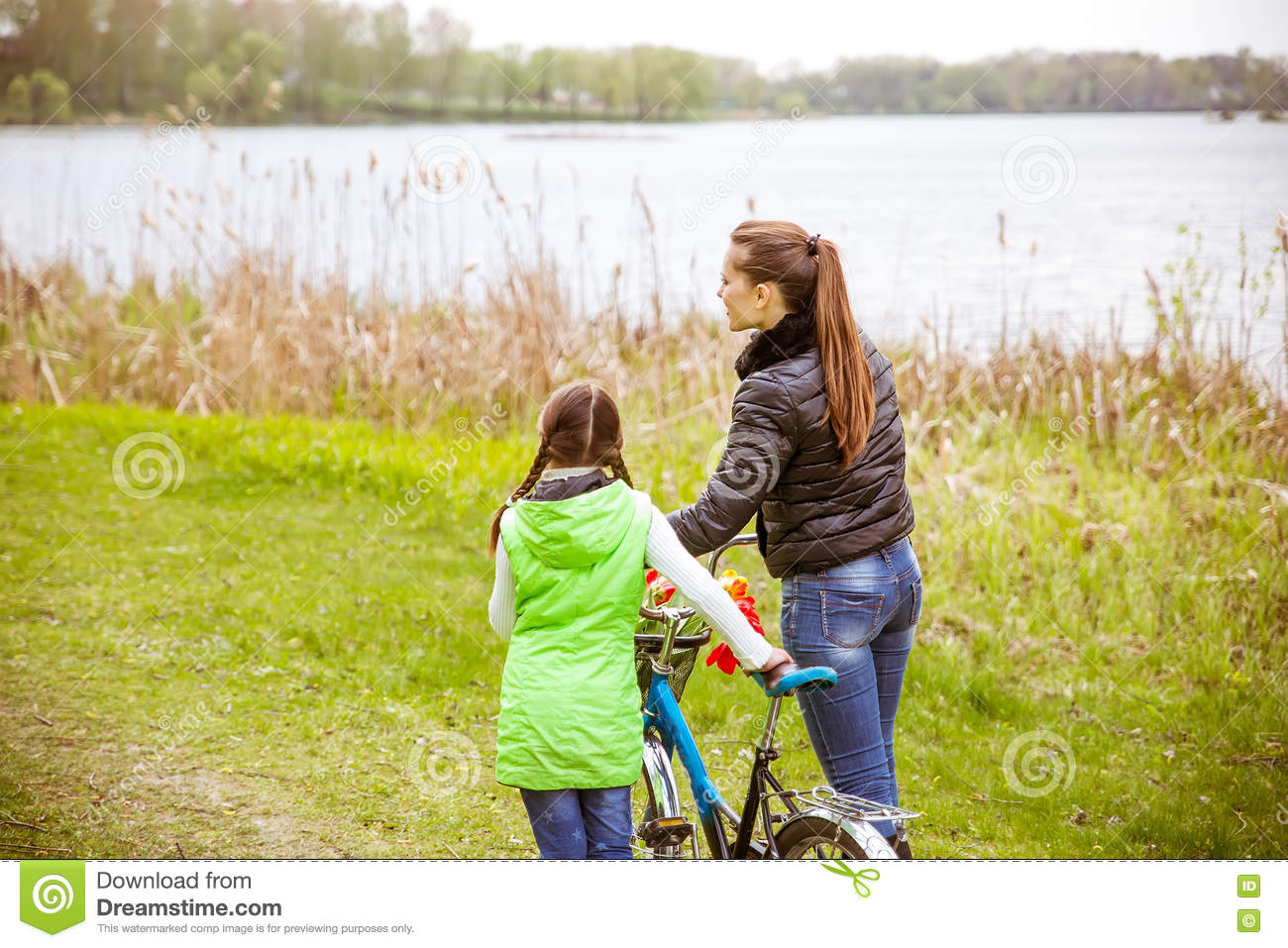 Daughter and mother walk along the shore of the lake with a bike and talk. Family values, education
