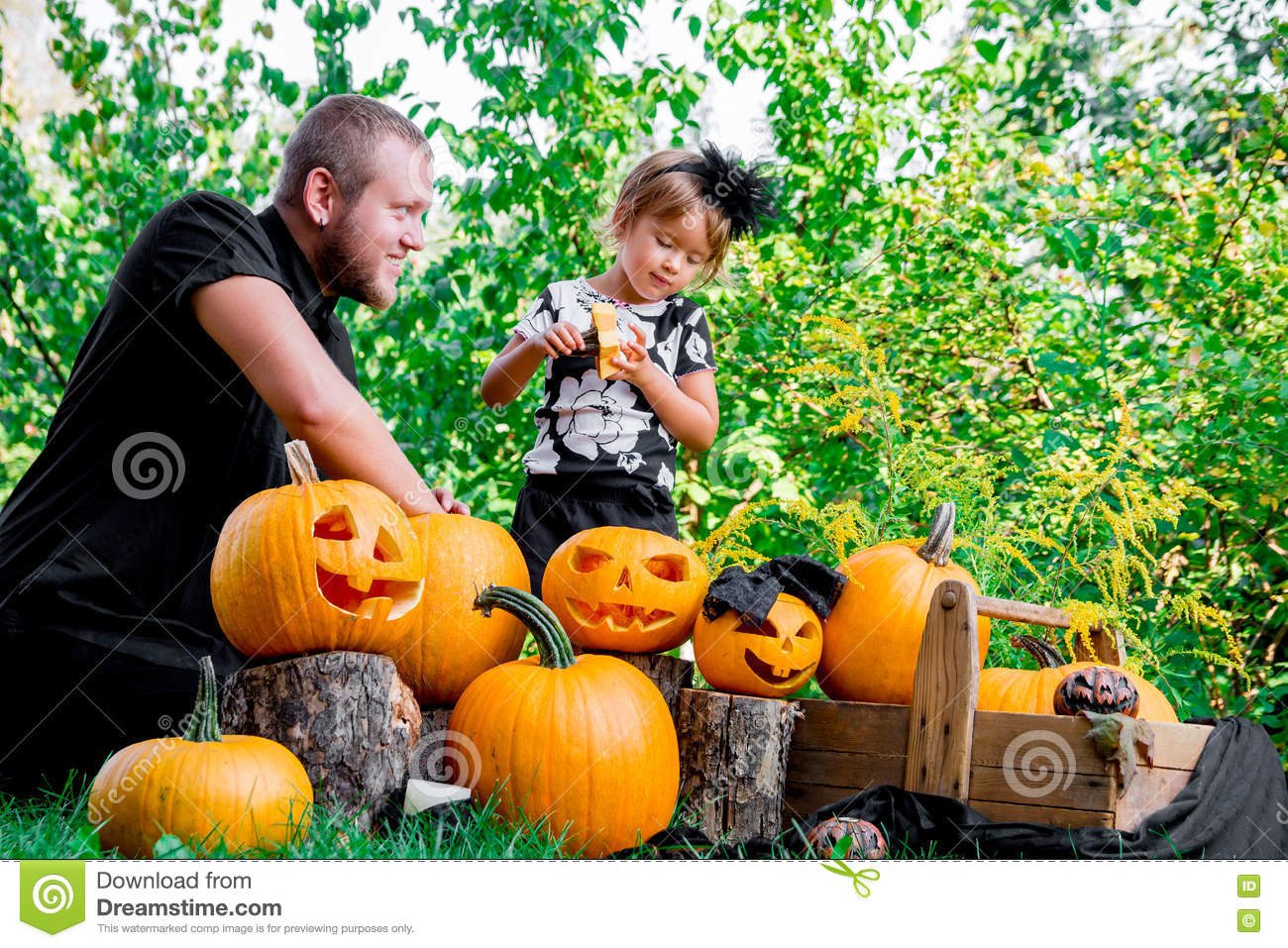 Daughter near father who pulls seeds and fibrous material from a pumpkin before carving for Halloween. Prepares jack-o-lantern. D