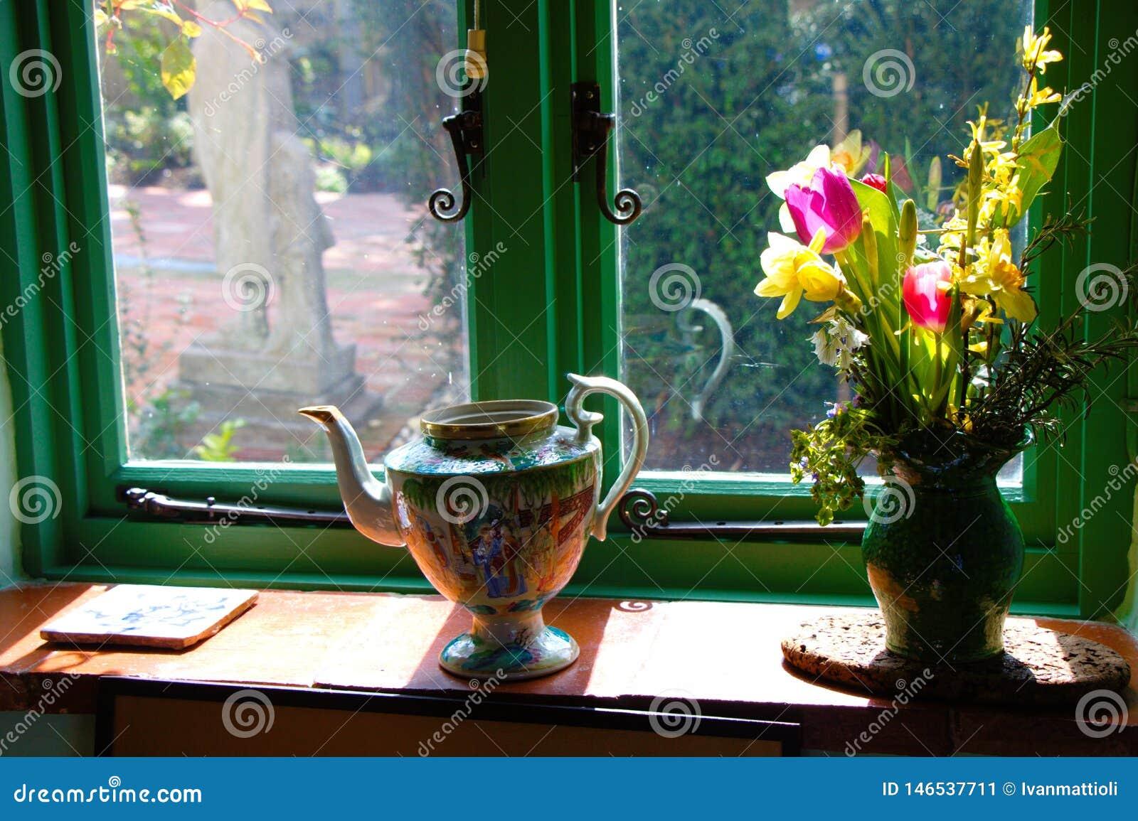 Davanzale decorato della finestra con i fiori in un vaso ed in una brocca del tè
