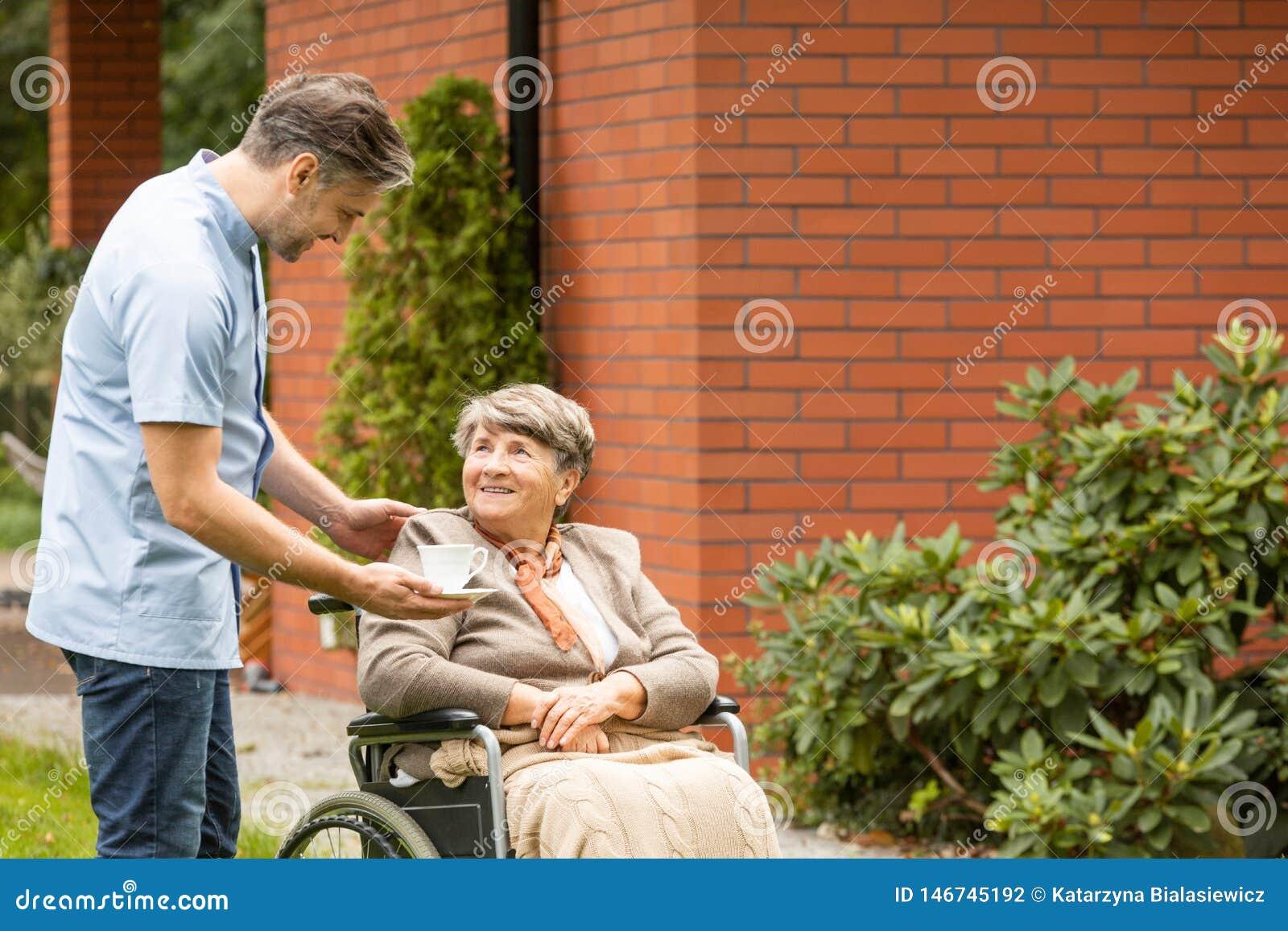 Dawać filiżance herbata uśmiechać się niepełnosprawnej starszej kobiety w wózku inwalidzkim