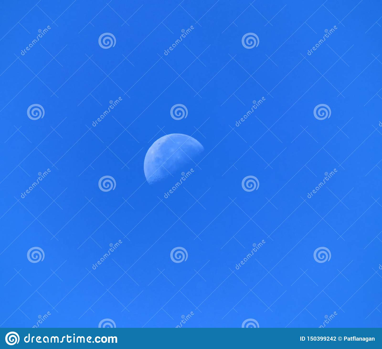 A day moon in a blue sky background