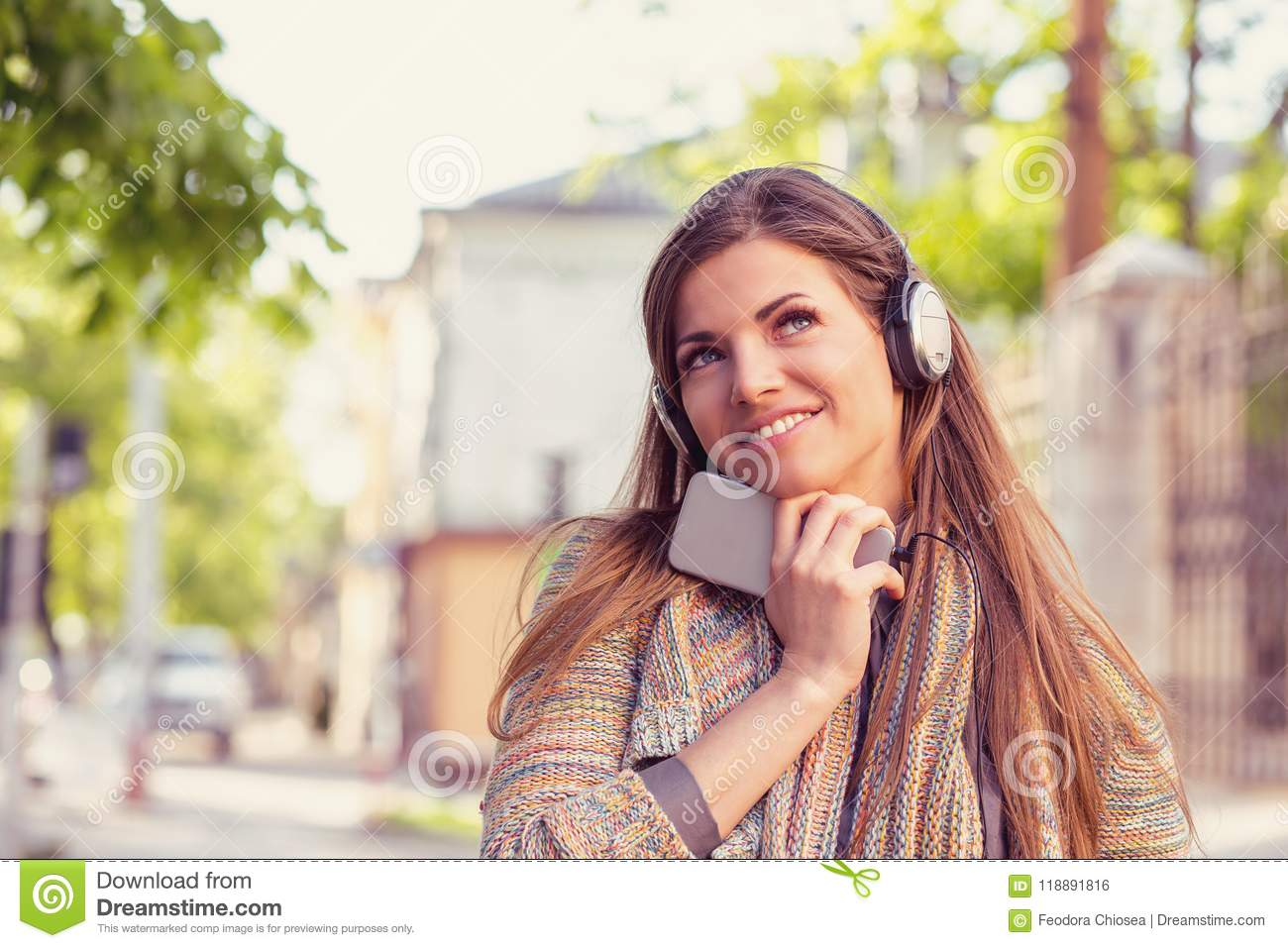 Daydreaming woman listening to the music on a smart phone walking down the street on an autumn sunny day