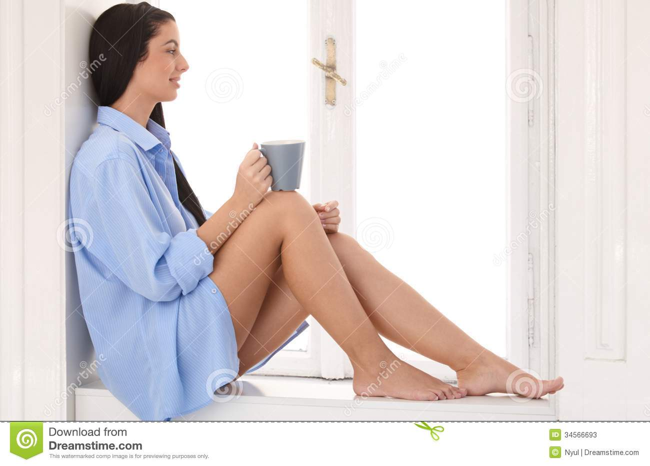 daydreaming woman sitting at window sill stock image