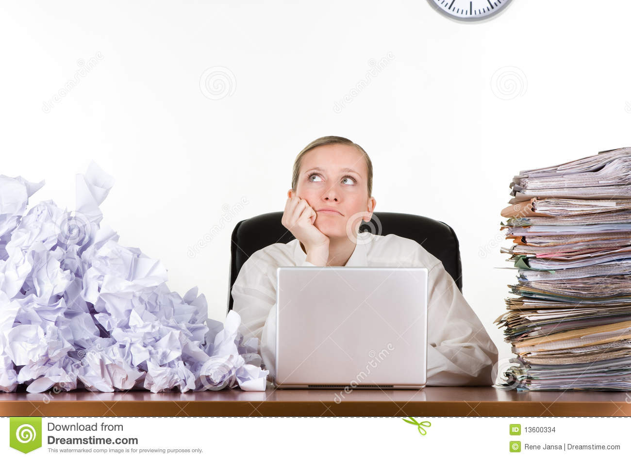 woman sitting at her desk and daydreaming while work piles up. .