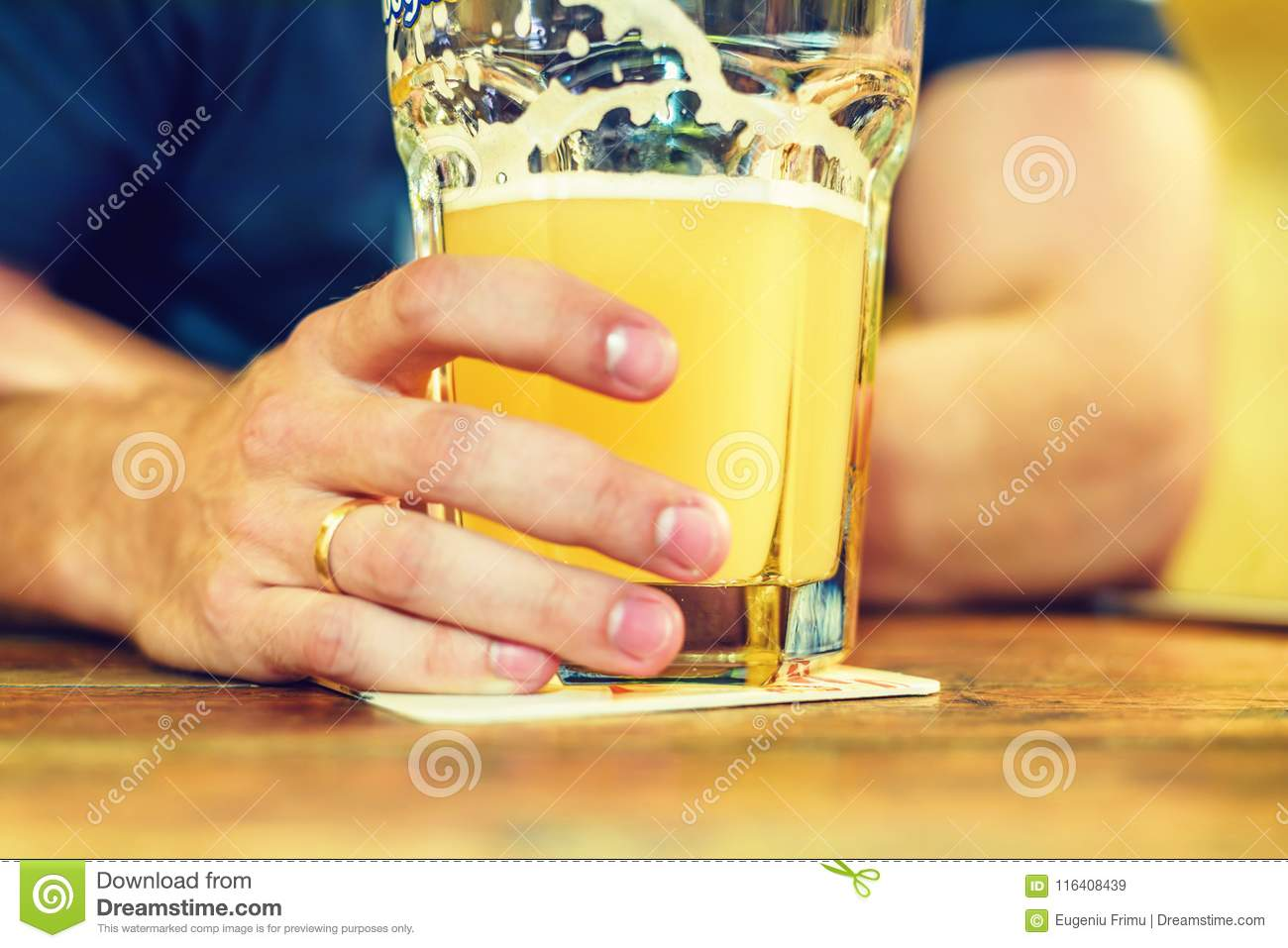 Daylight view to married man with golden ring drinking beer
