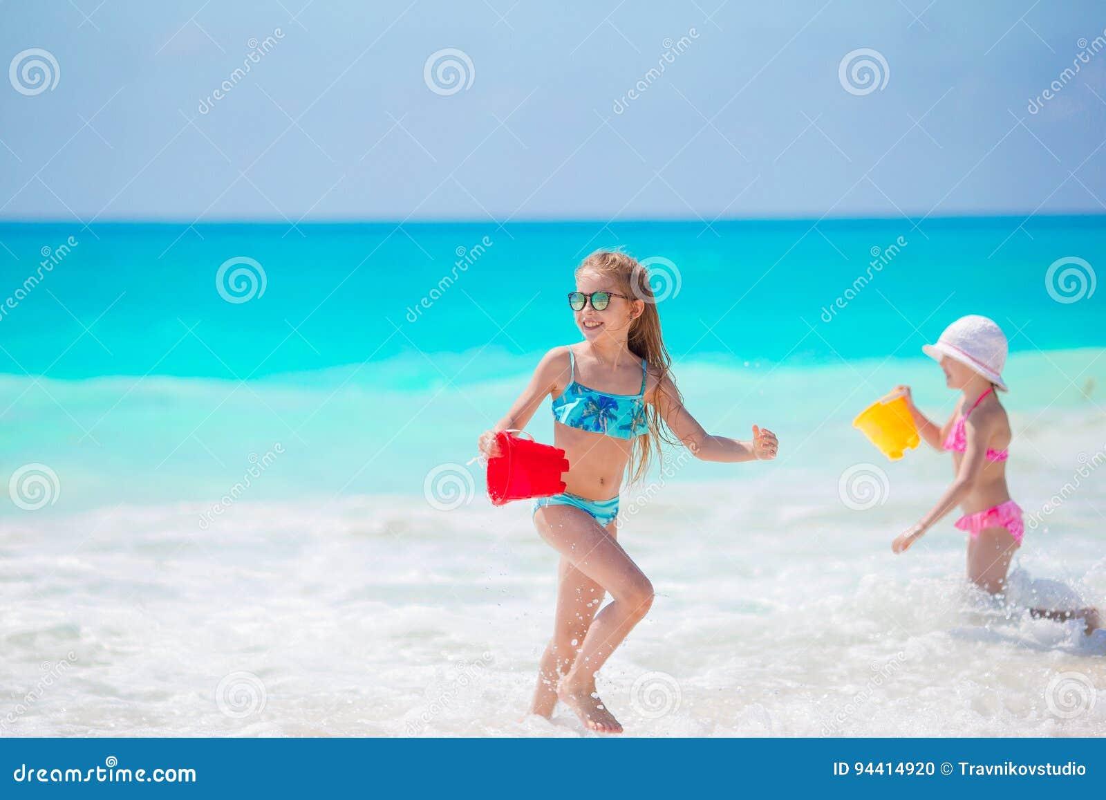 De aanbiddelijke meisjes hebben samen pret op wit tropisch strand
