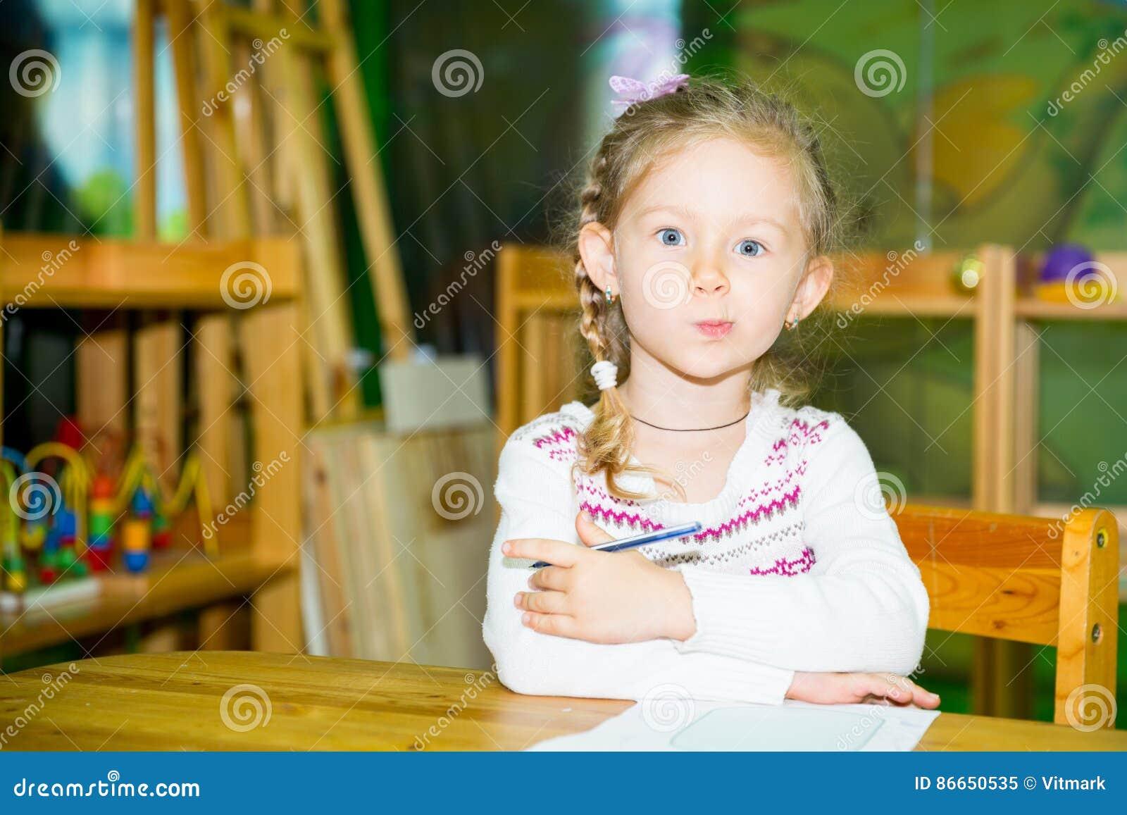 De aanbiddelijke tekening van het kindmeisje met kleurrijke potloden in kinderdagverblijfruimte Jong geitje in kleuterschool in d