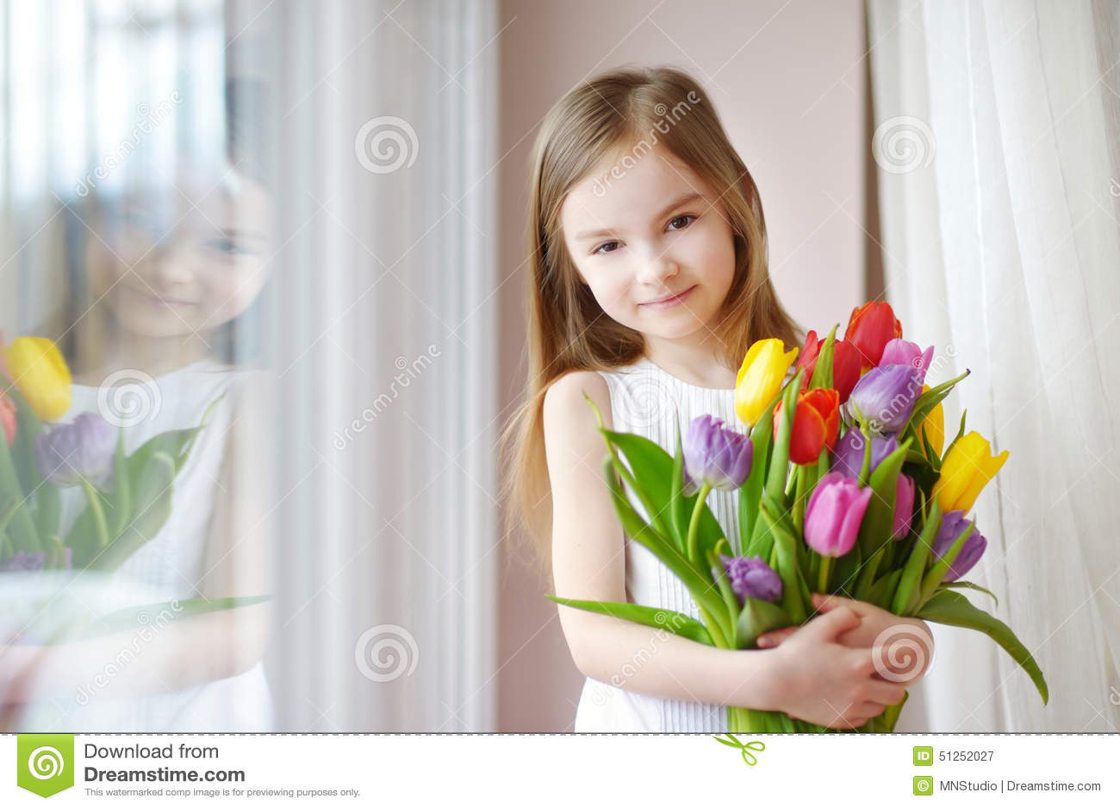 De aanbiddelijke tulpen van de meisjeholding door het venster