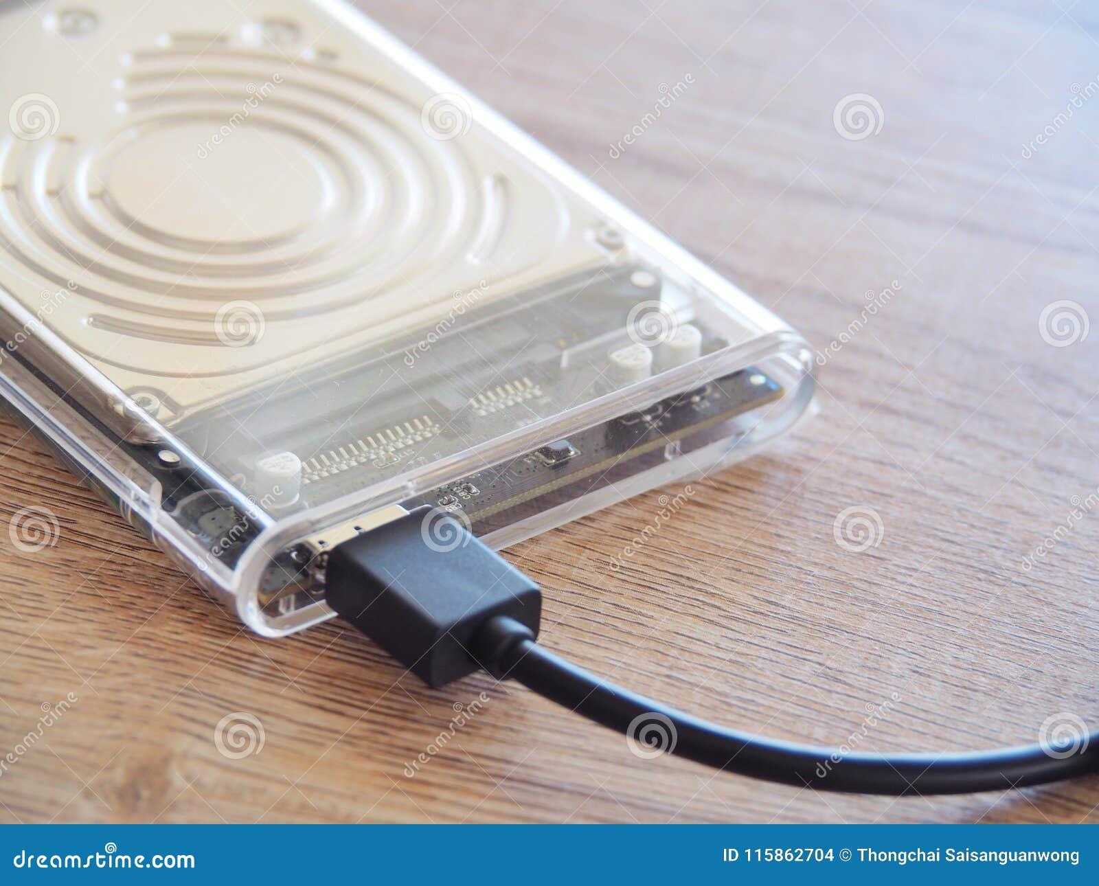 De aandrijving wordt verbonden met een notitieboekjecomputer op een houten bureau Met het concept het houden van informatie in de