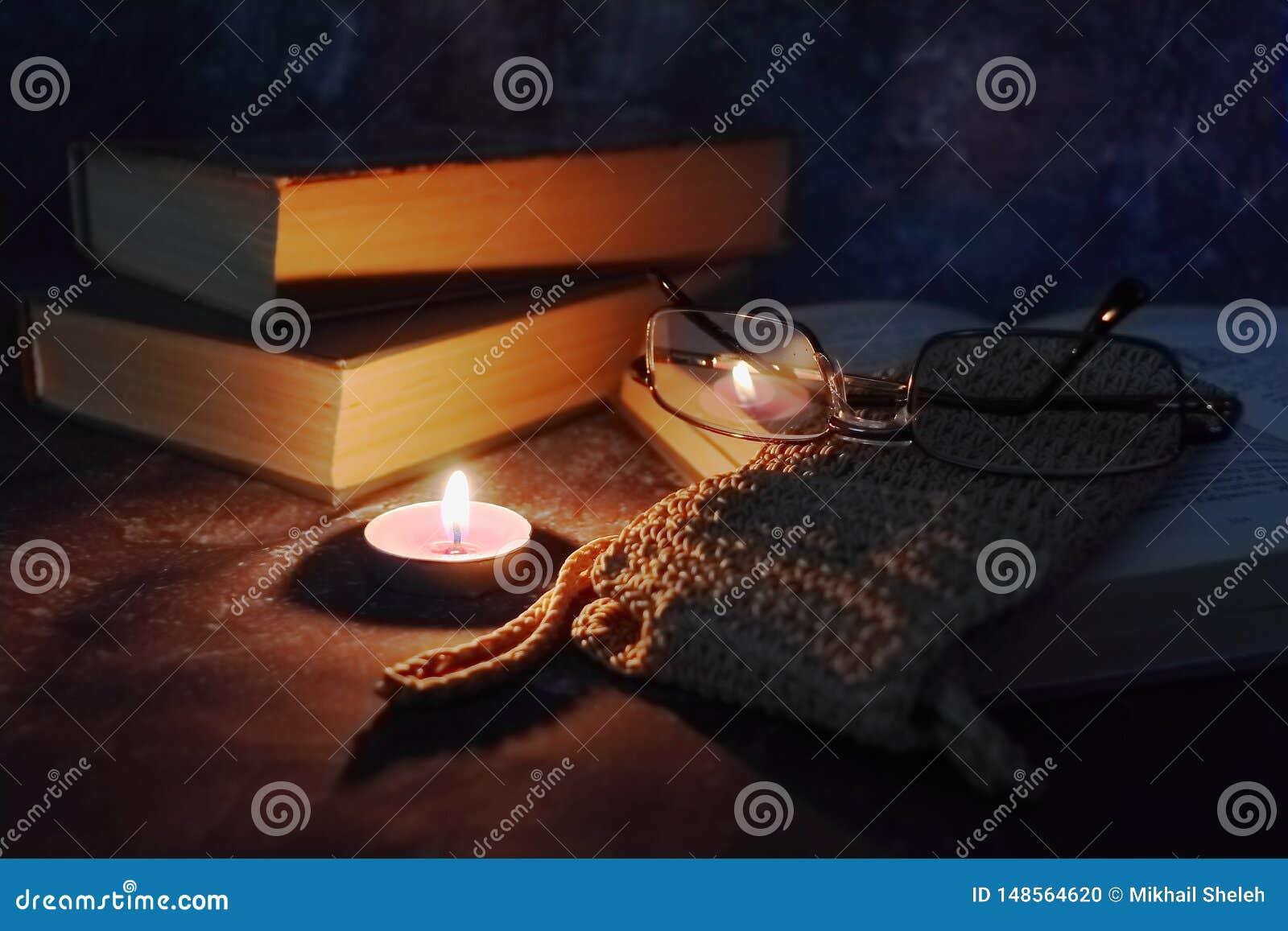 De aangestoken kaarsen in het vertrouwelijke plaatsen, oude boeken, vergeelden van tijd tot tijd, glazen in een gebreide gele dra