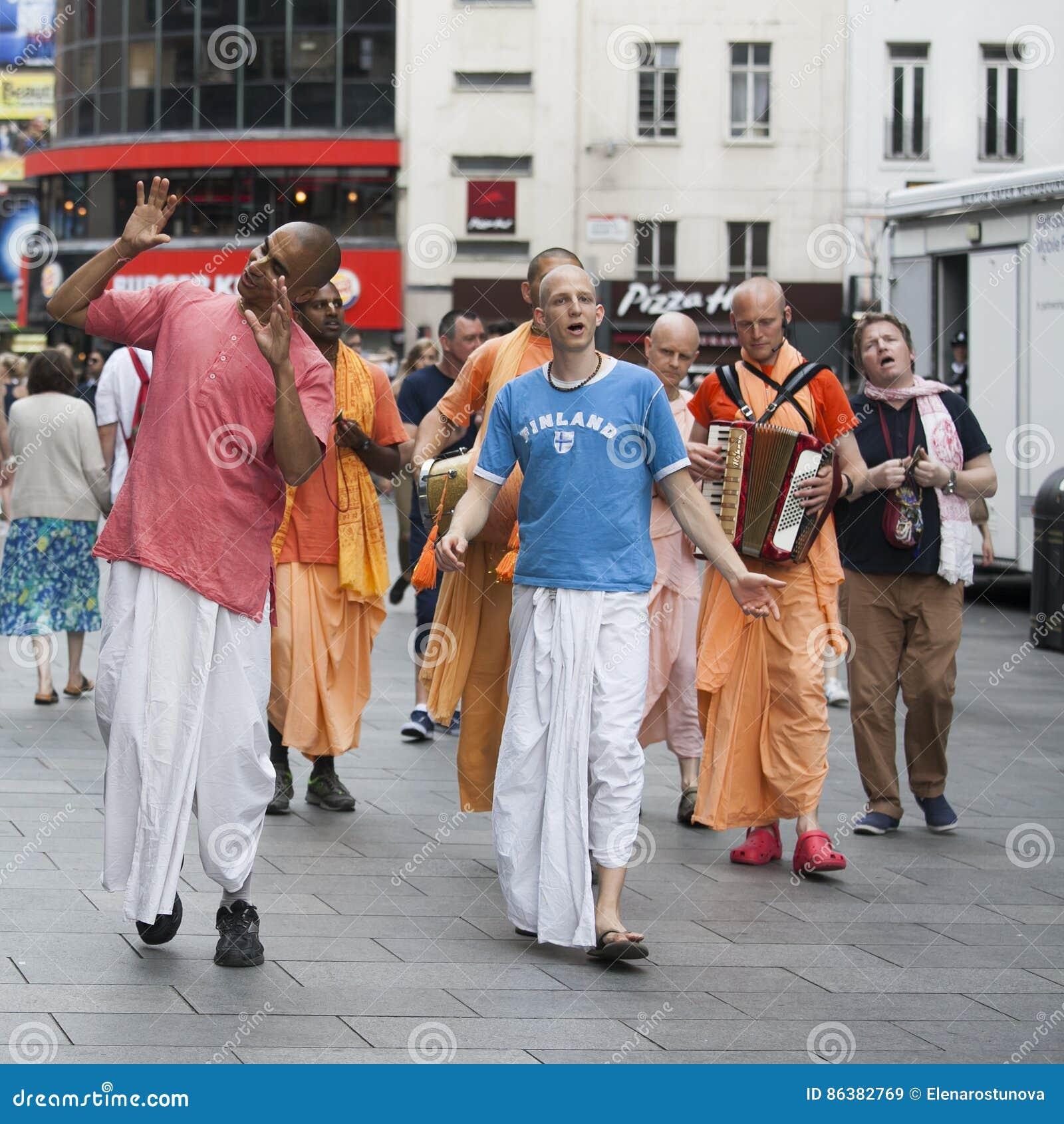 De aanhangers van hazenkrishna lopen onderaan de Straat van Londen ` s Oxford in hun oranje robes