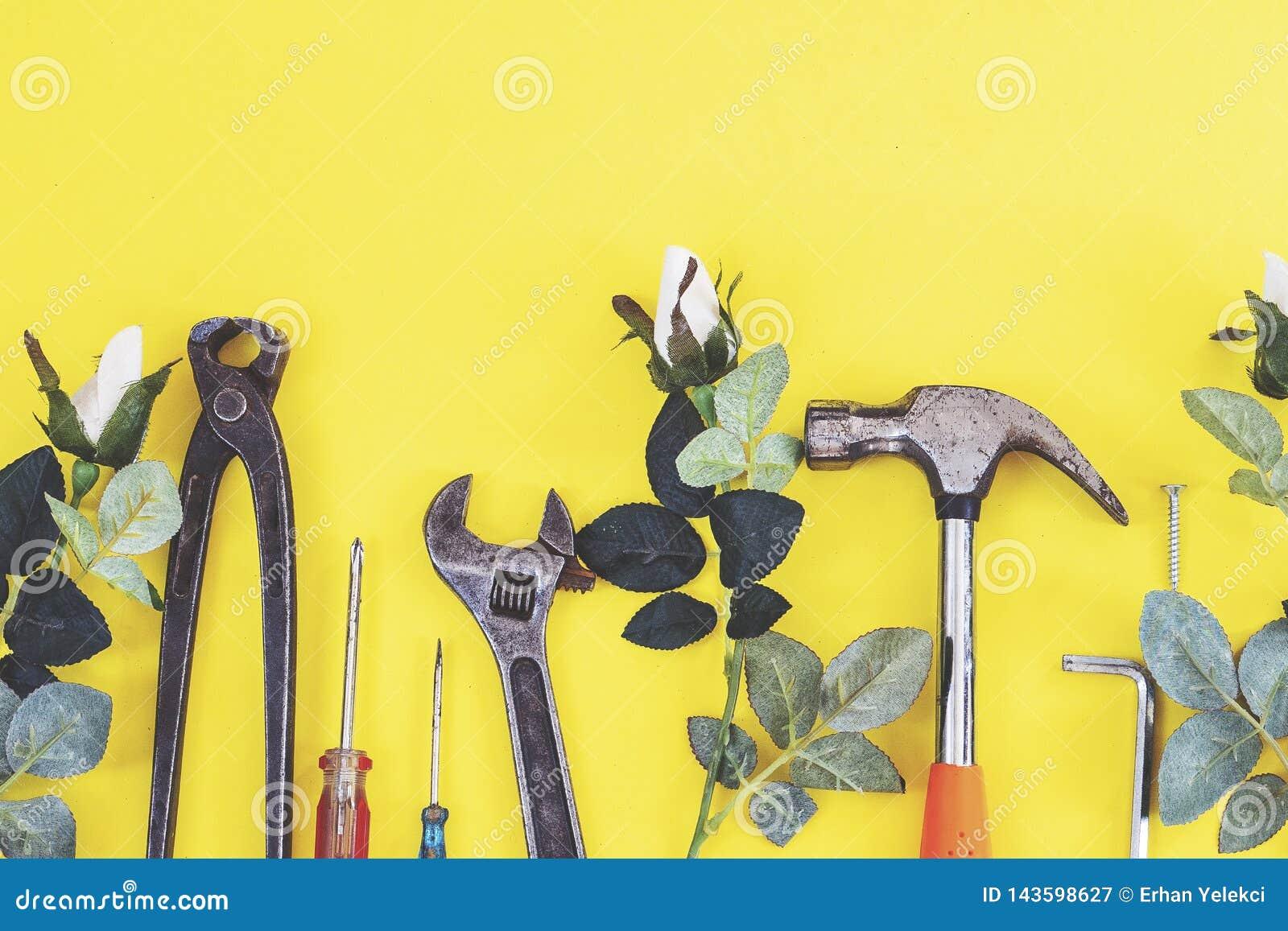 De aannemershulpmiddelen van de moersleutelingenieur op een denimarbeiders, de gele achtergrond van A met de hulpmiddelen van de