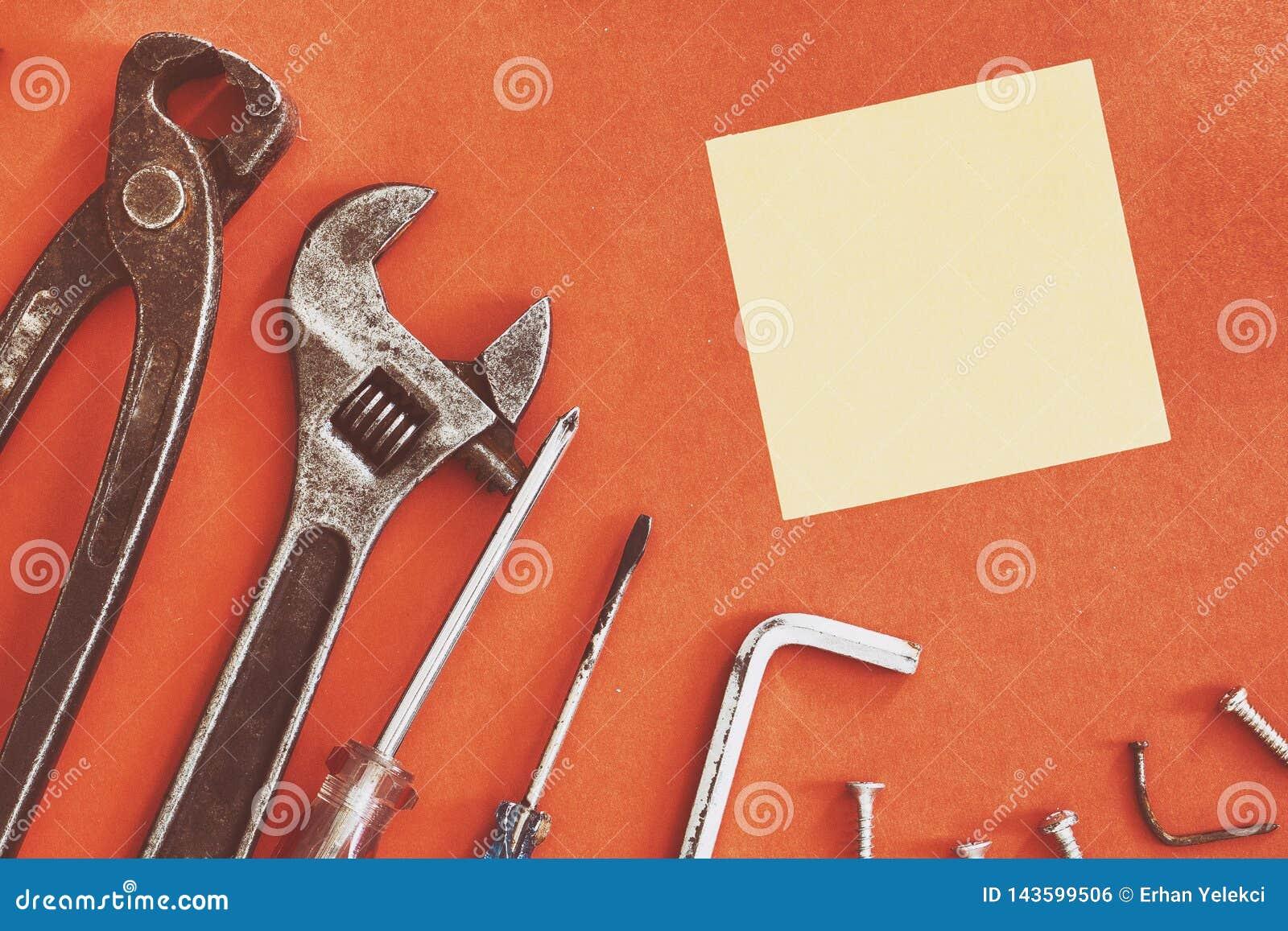De aannemershulpmiddelen van de moersleutelingenieur op een denimarbeiders, de rode achtergrond van A met de hulpmiddelen van de