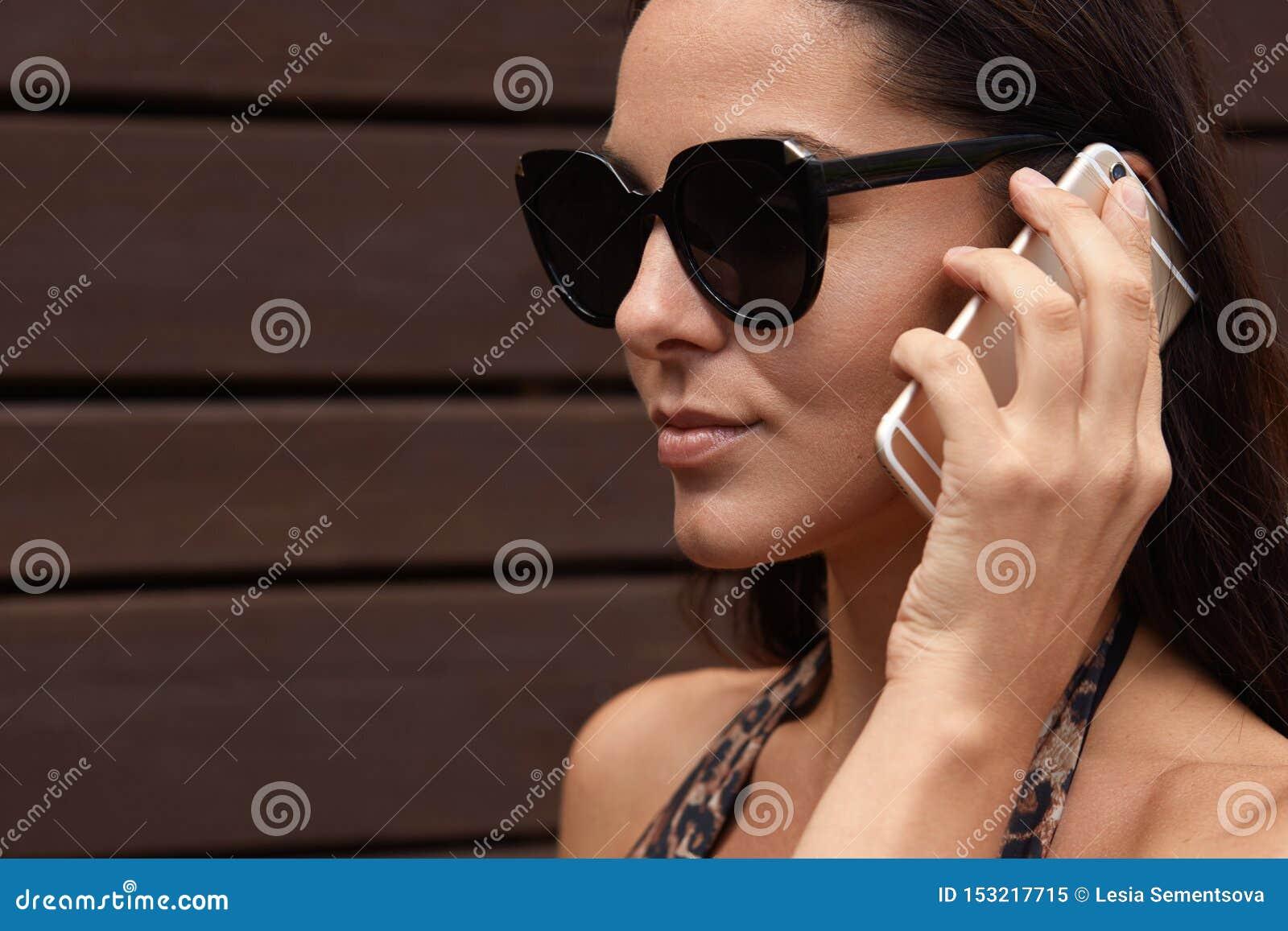 De aantrekkelijke donkerbruine vrouw in donkere zonnebril heeft telefoongesprek in openlucht op mobiele telefoon, bekijkend afsta