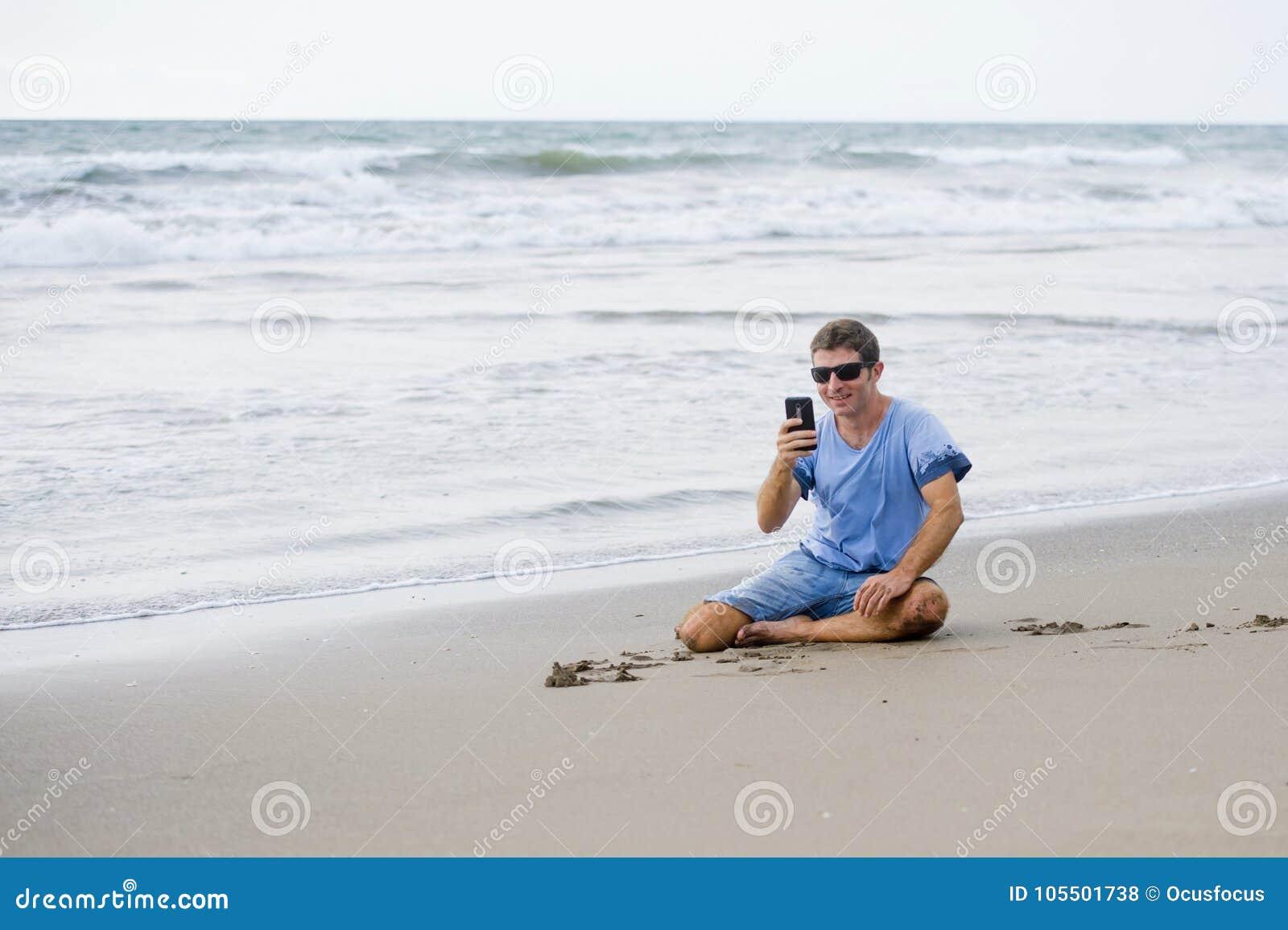 De aantrekkelijke en knappe mens die op zijn jaren  30 op het zand zitten ontspande op het strand lachend voor het overzees die o