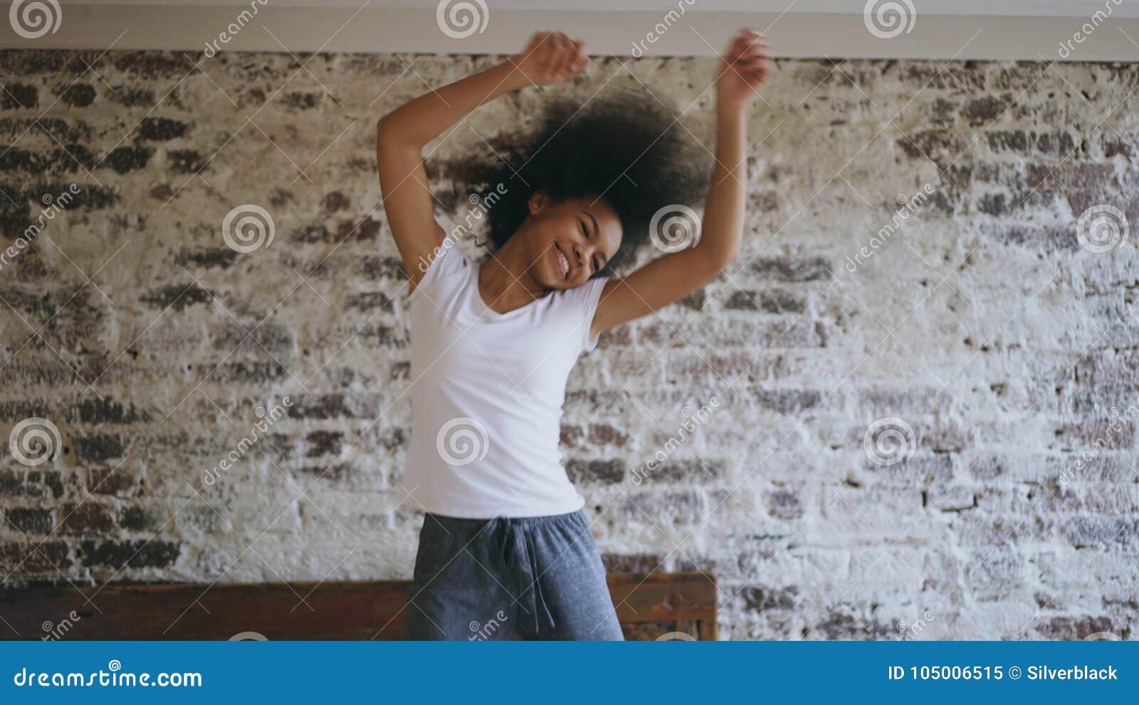 De aantrekkelijke gemengde ras jonge blije vrouw heeft pret thuis dansend dichtbij bed