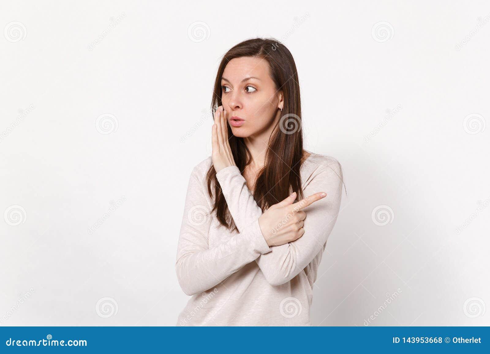 De aantrekkelijke jonge vrouw fluistert roddel en vertelt geheim met handgebaar, die wijsvinger richten die opzij op wit wordt ge