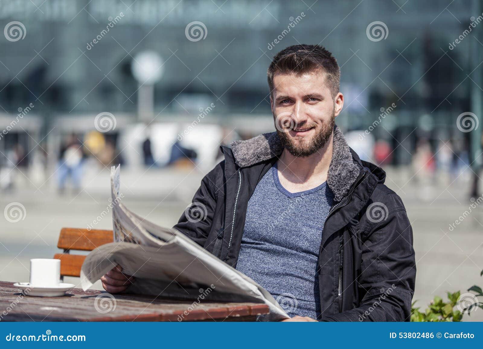 De aantrekkelijke mens zit in een koffiewinkel lezend de krant