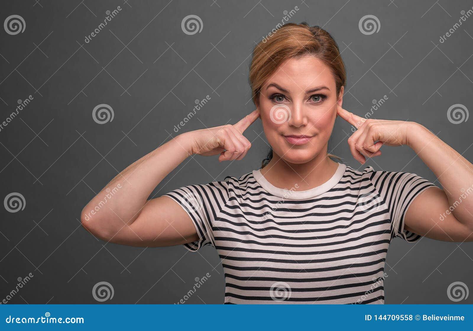 De aantrekkelijke vrouw behandelt haar oren met vingers op een grijze achtergrond