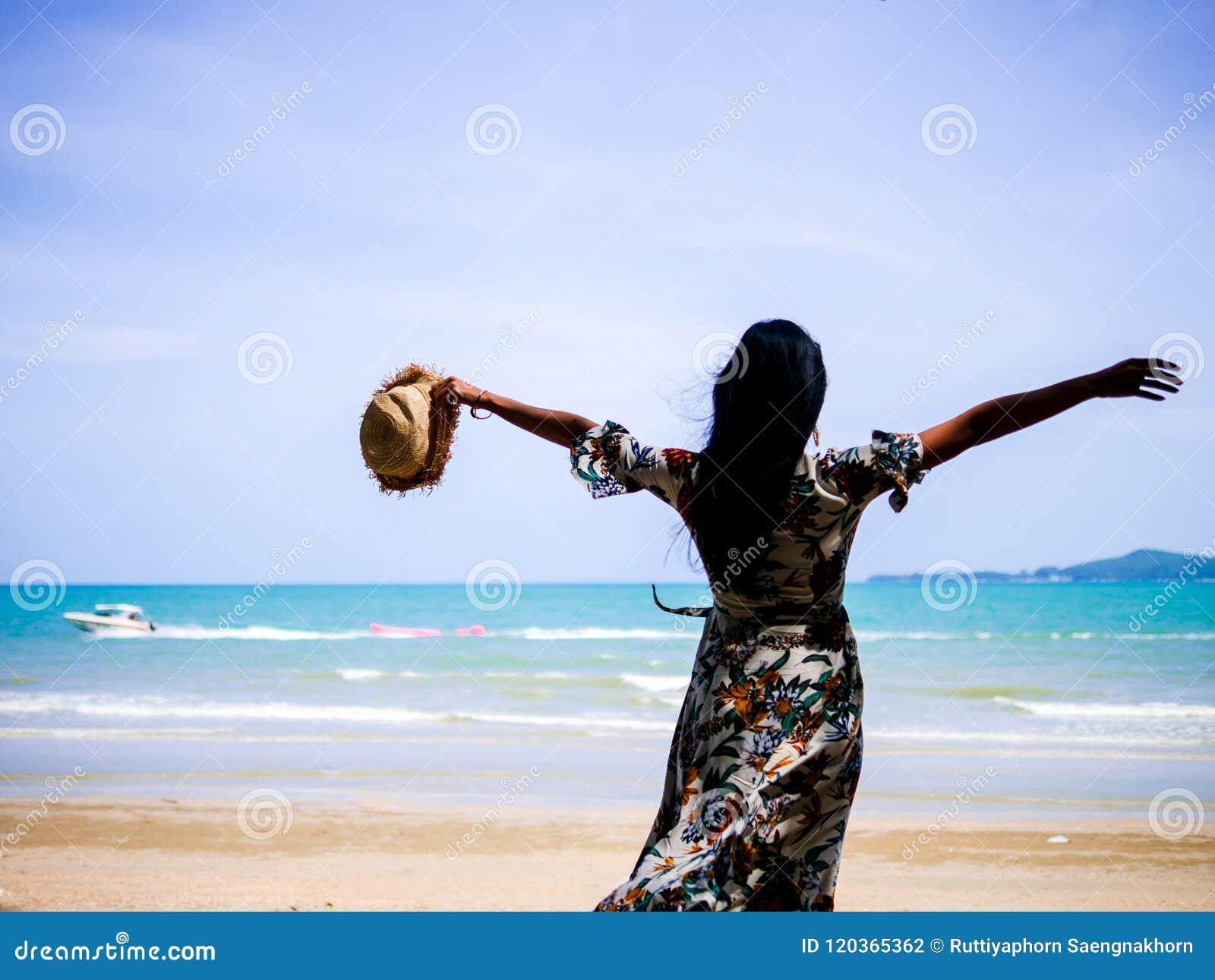 De aantrekkelijke vrouw die uitstekende kleren dragen die hoed in hand houden en rekt de wapens bij kust uit