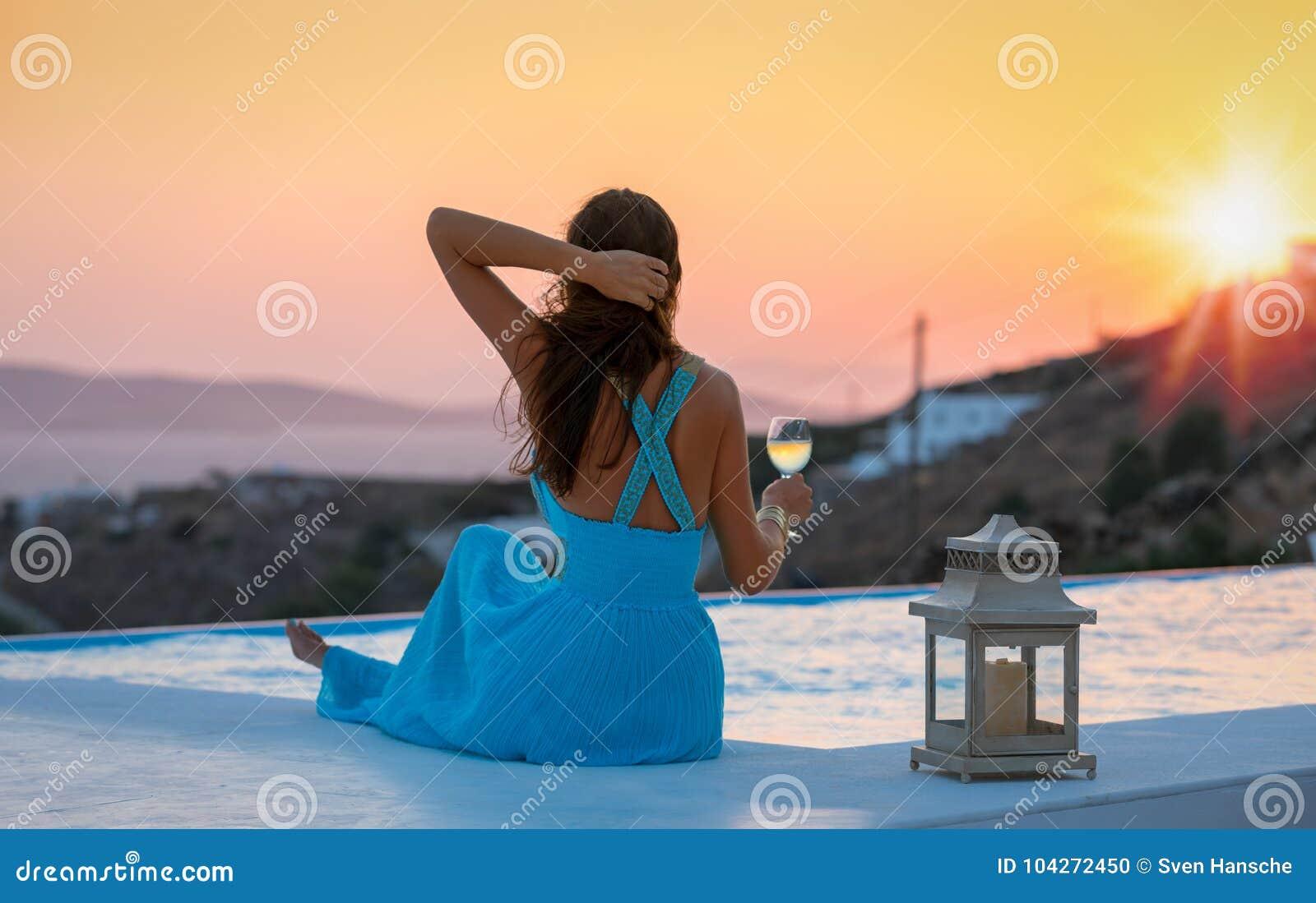 De aantrekkelijke vrouw geniet van de de zomerzonsondergang