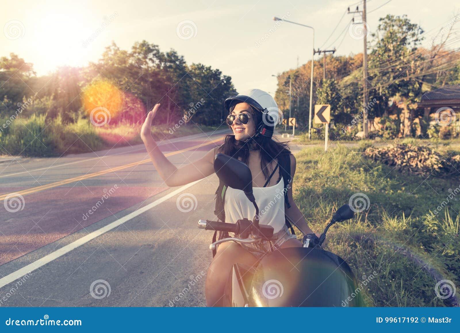 De aantrekkelijke Vrouw geniet Zon van Gloed op Motorfietsslijtage Helemt op Reis van de de Vrouwenmotorrijder van de Plattelands