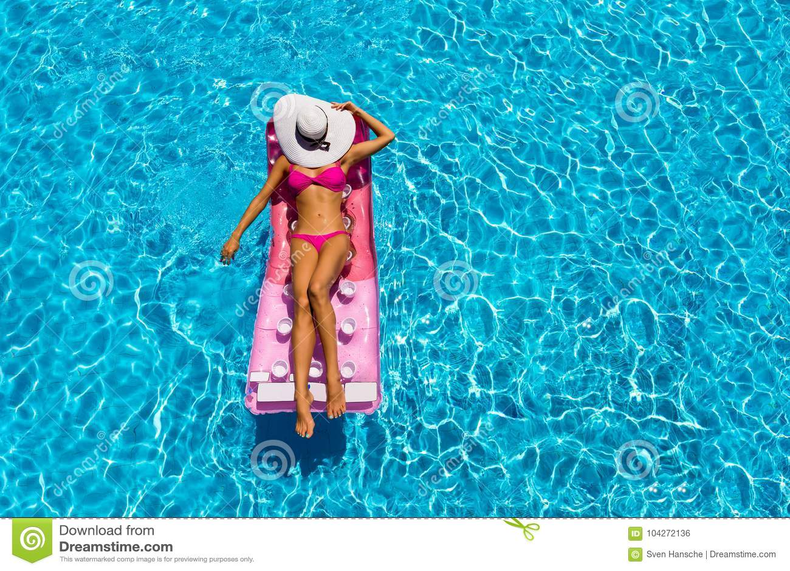 De aantrekkelijke vrouw ontspant op een drijvende matras in een pool