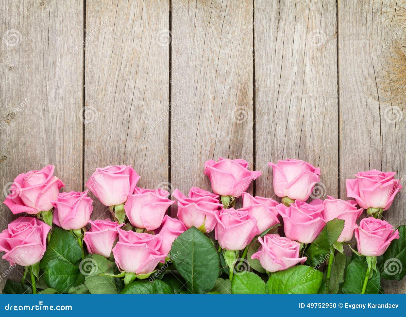 De achtergrond van de valentijnskaartendag met roze rozen over houten lijst