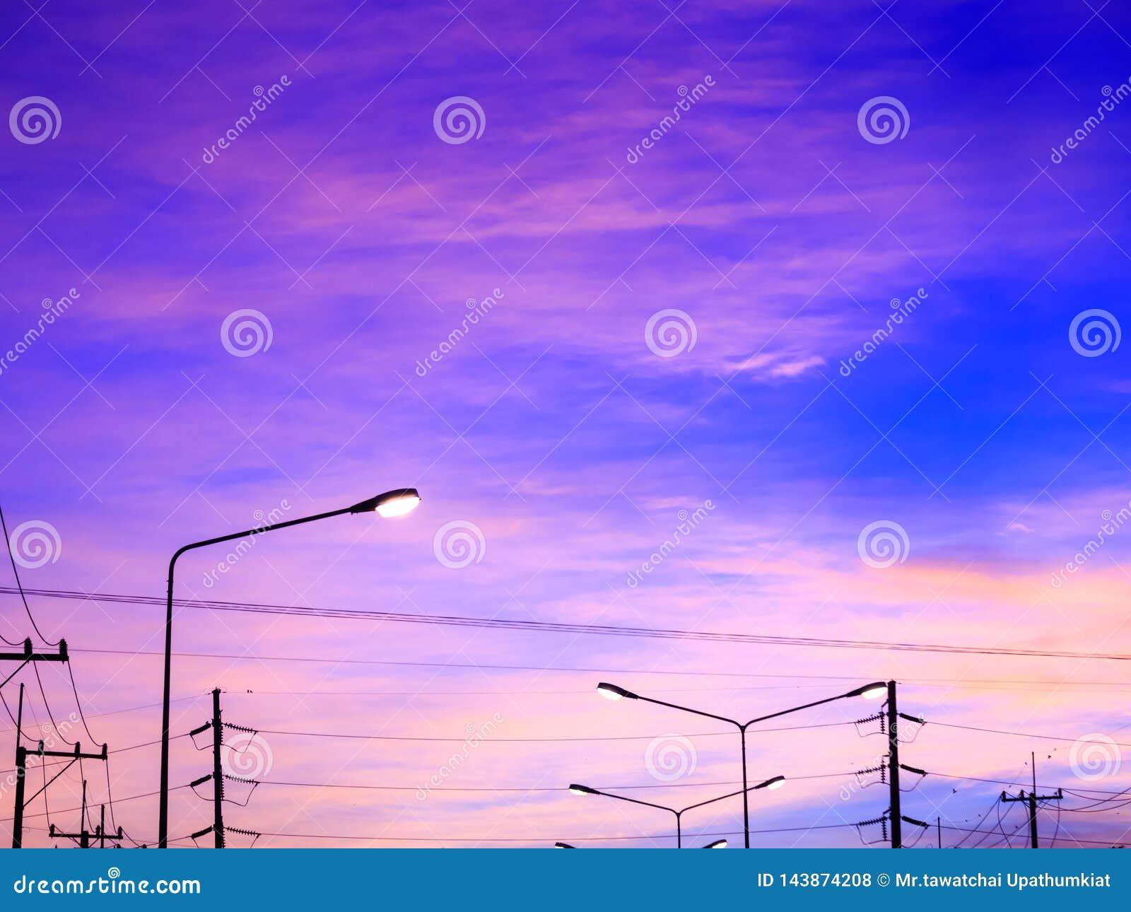 De achtergrond van de fantasiehemel met roze wolken en hoogtepunt van straatlantaarn na zonsondergang