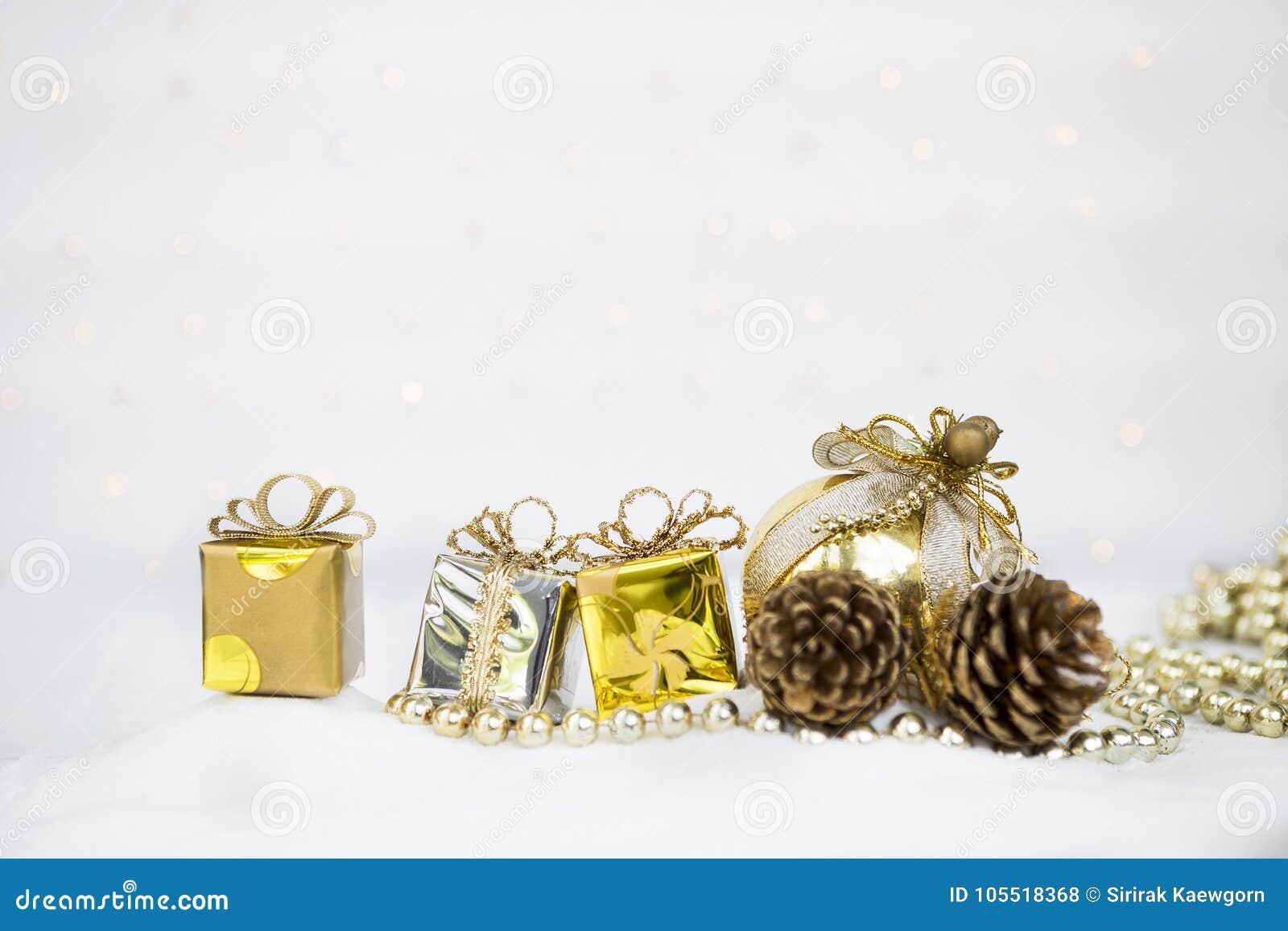 De achtergrond van het Kerstmisconcept, giftdoos met denneappel en gouden bal over vaag licht bokeh