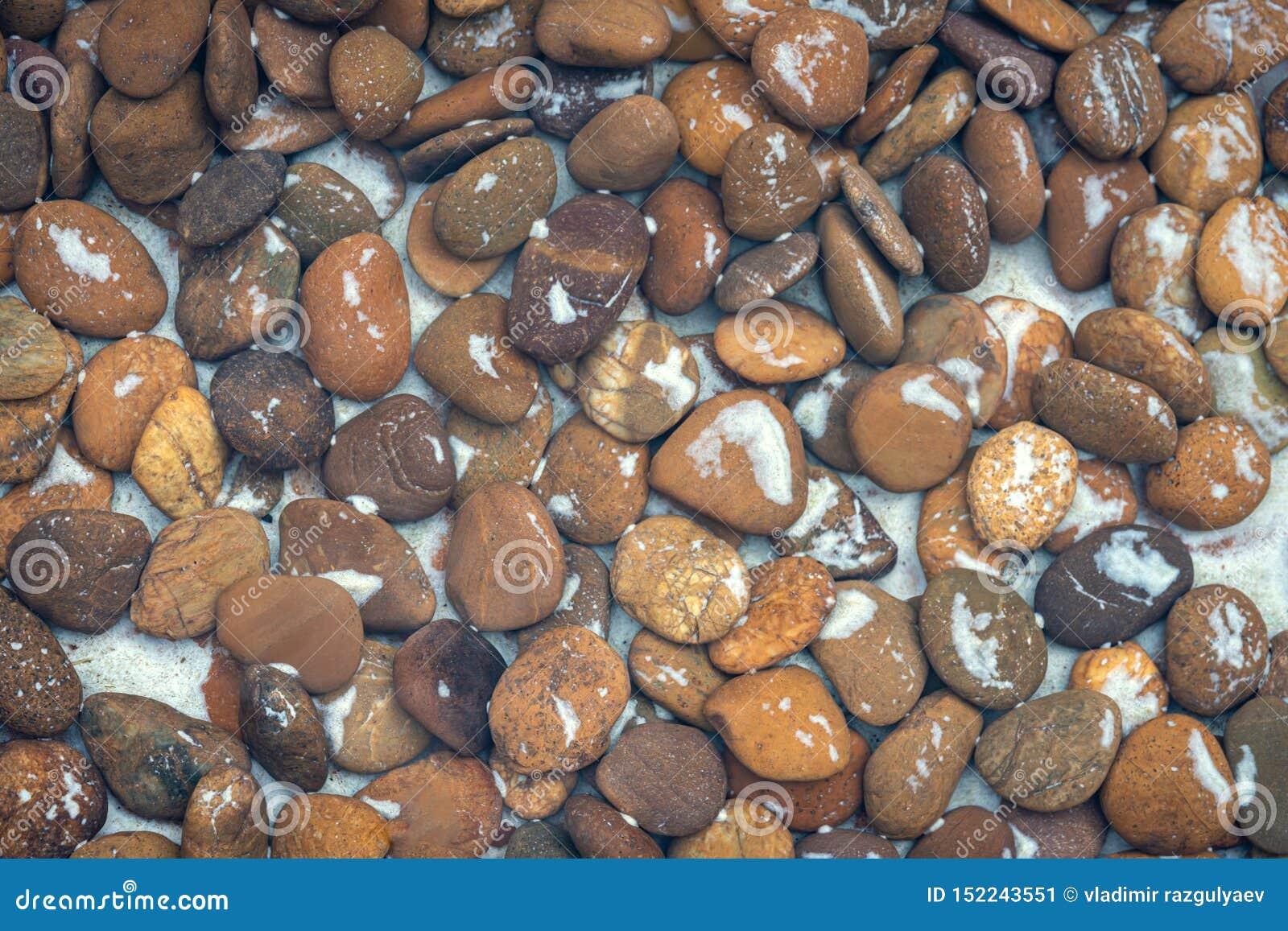 De achtergrond van het steenpatroon de stenen die in het water liggen