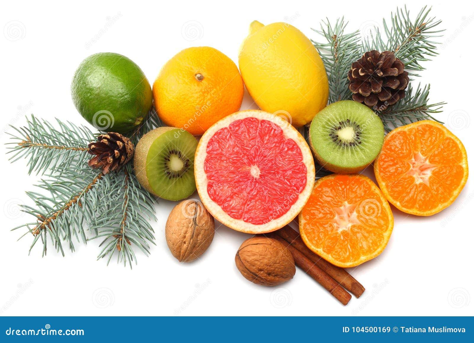 De achtergrond van Kerstmis de mengeling sneed citroen, groene kalk, sinaasappel, mandarin, kiwifruit en grapefruit met kegel en