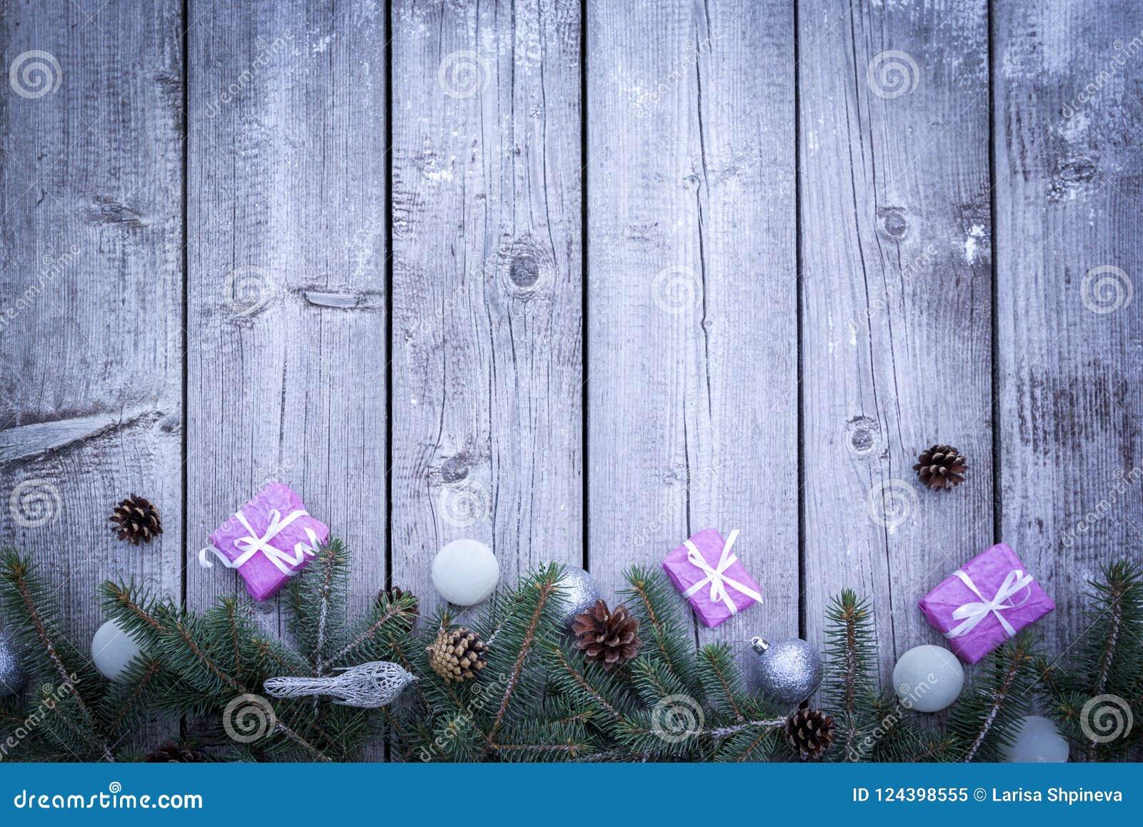 De achtergrond van de Kerstmisvakantie met giftenvakjes met spar vertakt zich, denneappels, Kerstmisballen op houten lijst Vlak l
