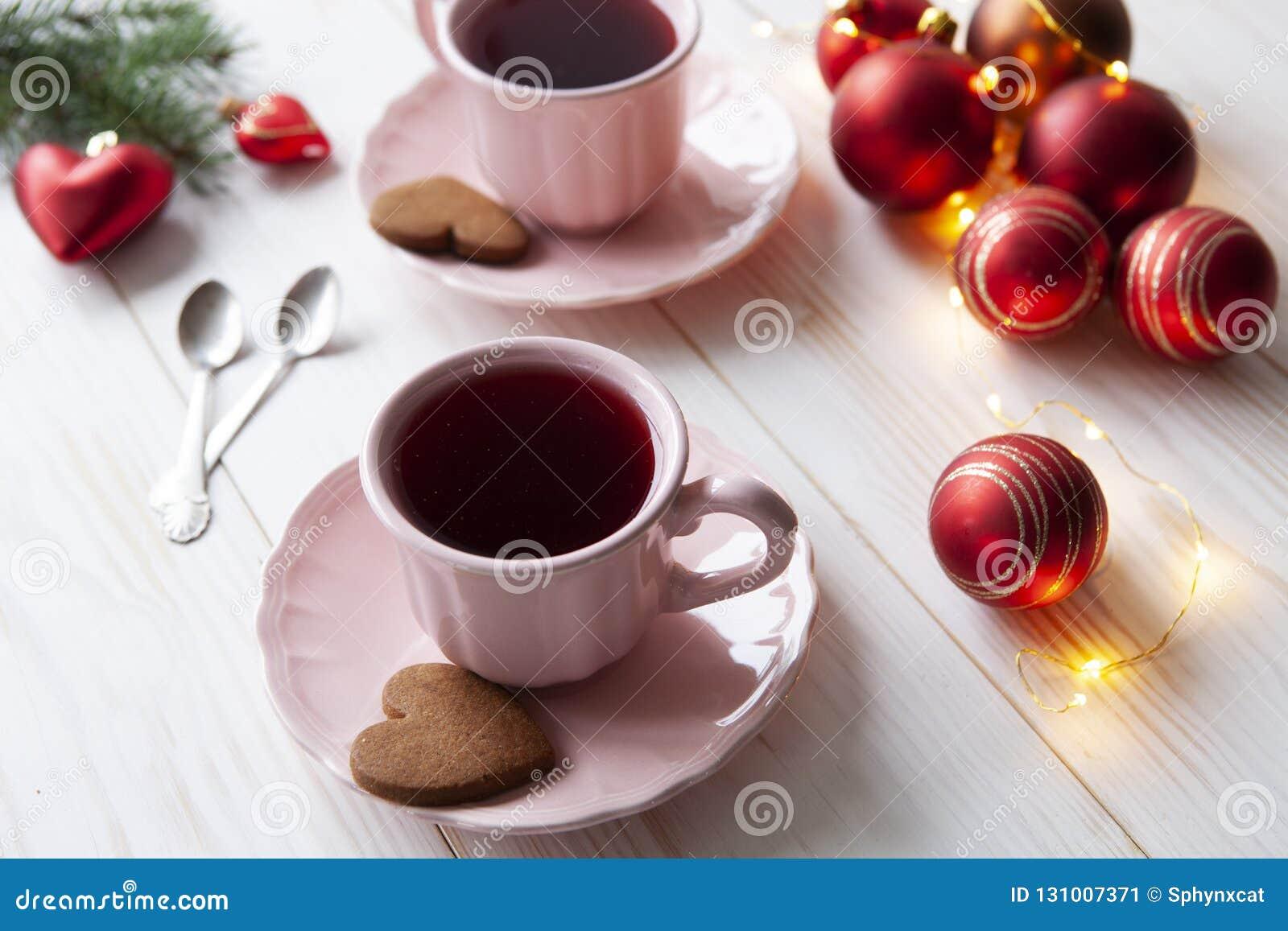 De achtergrond van de Kerstmisvakantie met twee kop theeën en koekjes