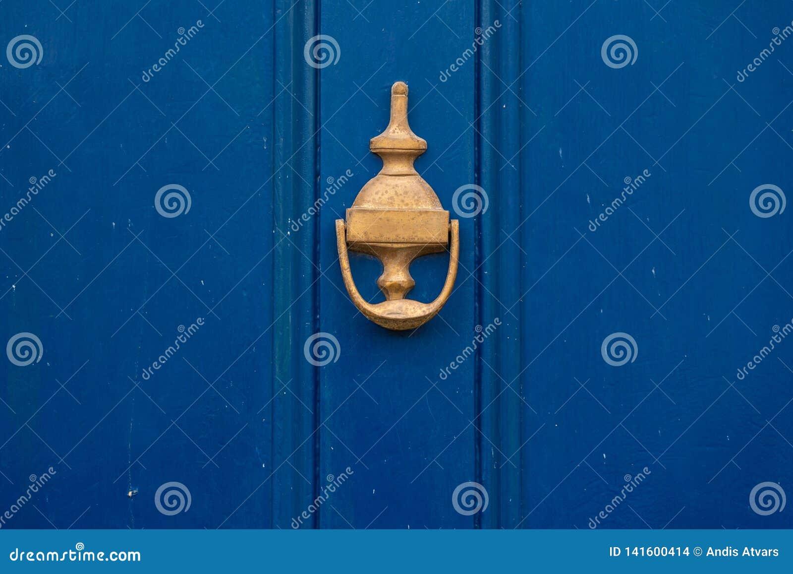 De achtergrond van uitstekende blauwe geschilderde deur en kloppersvignet kijkt die van ouderwets uitstekend messingsmetaal wordt