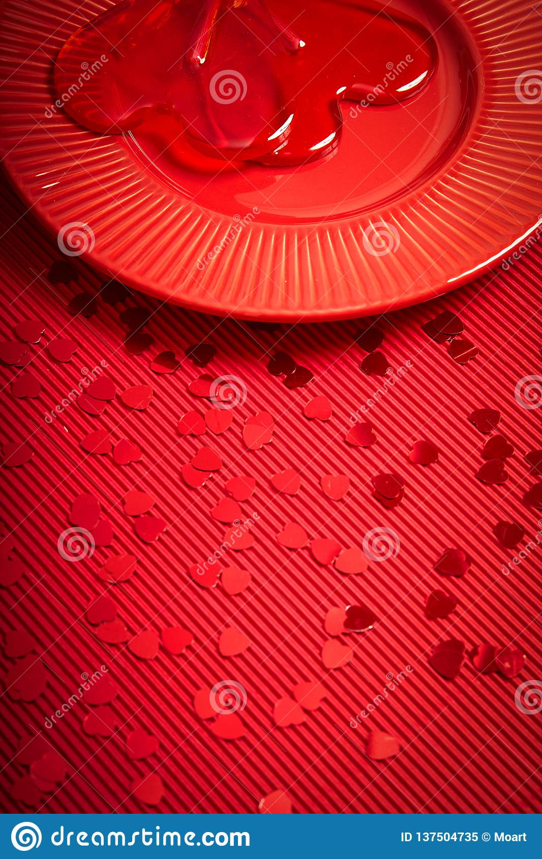 De achtergrond van de valentijnskaartendag met rood geribbeld document met rode plaat en hart-vormige lolly