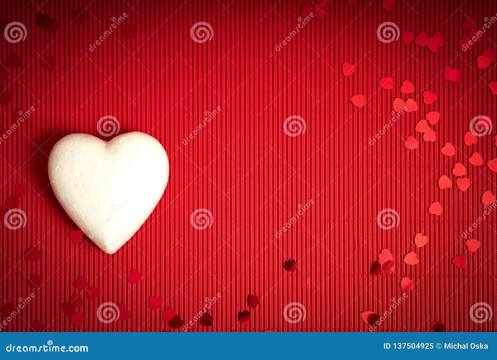 De achtergrond van de valentijnskaartendag met rood geribbeld document met witte storaxschuimharten voor minnaars