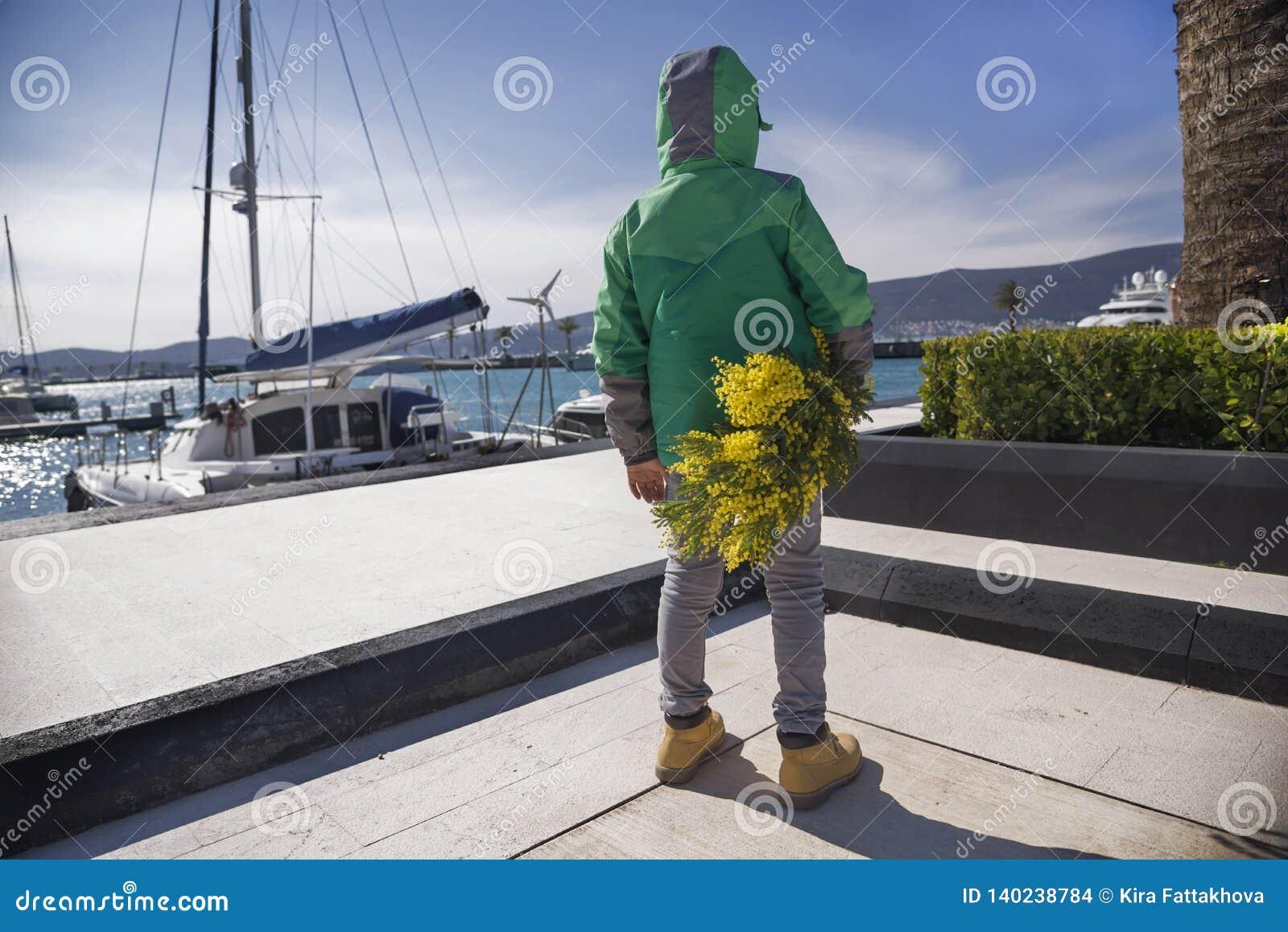 De achtermening bij weinig jong geitjejongen in Porto Montenegro, Montenegro, Tivat, springt de Zonnige bloemen van de dagholding
