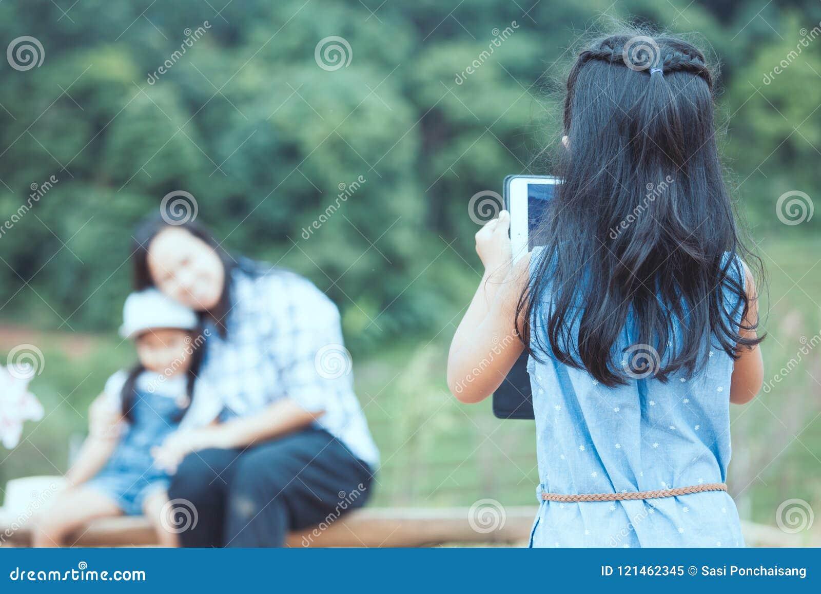 De achtermening van Aziatisch kindmeisje gebruikt tablet die een foto nemen