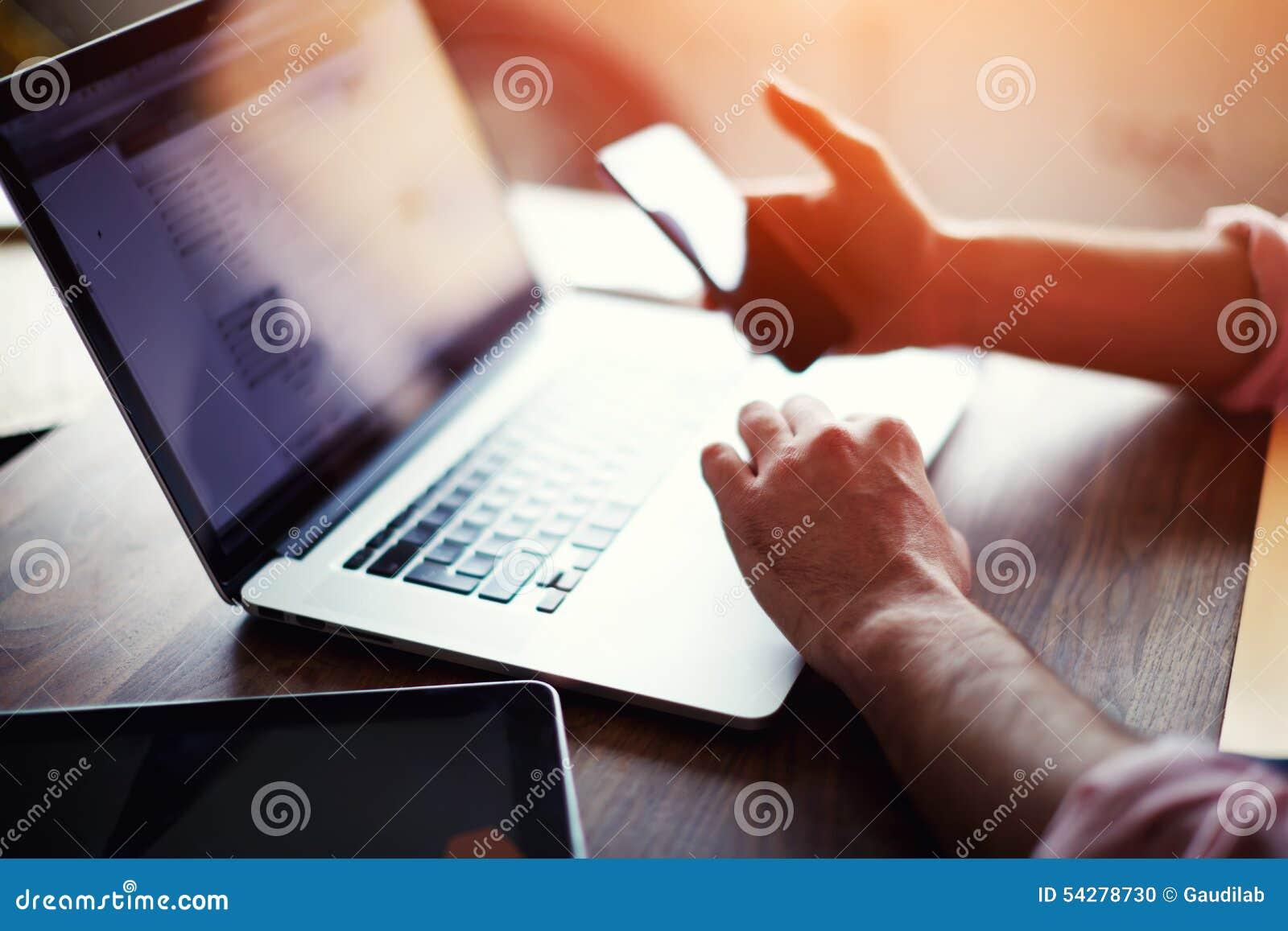 De achtermening van de bedrijfsmens overhandigt bezige gebruikende celtelefoon bij bureau
