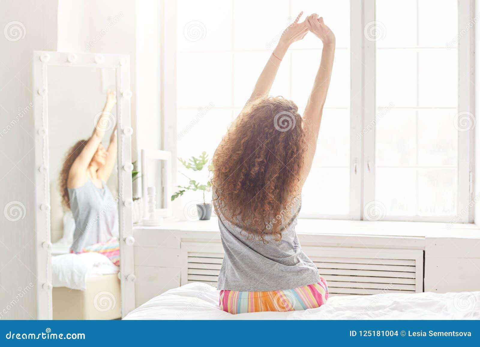 De achtermening van ontspannen vrouwenrek in bed, stelt dichtbij venster tegen comfortabel slaapkamerbinnenland, ontwaakt in ocht