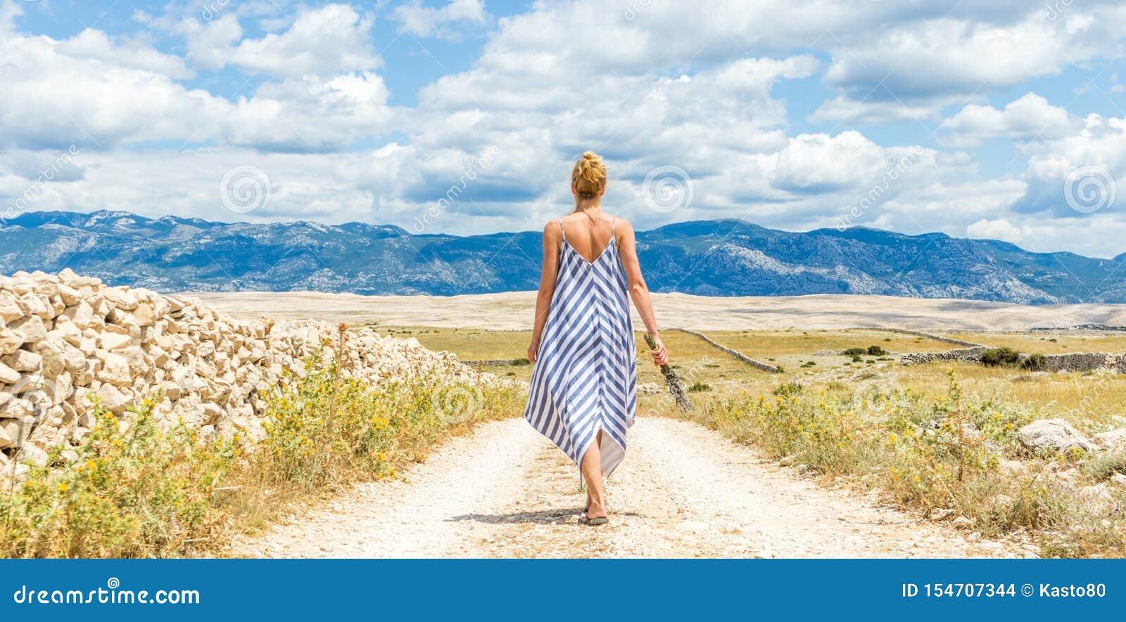 De achtermening van vrouw in de holdingsboeket van de de zomerkleding van lavendel bloeit terwijl lopen openlucht door droge rots