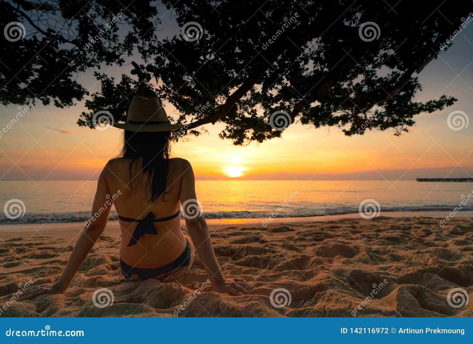 De achtermening van zwangere vrouw zit op zand en het letten op zonsondergang bij tropisch strand Het zwempak en het strohoed van